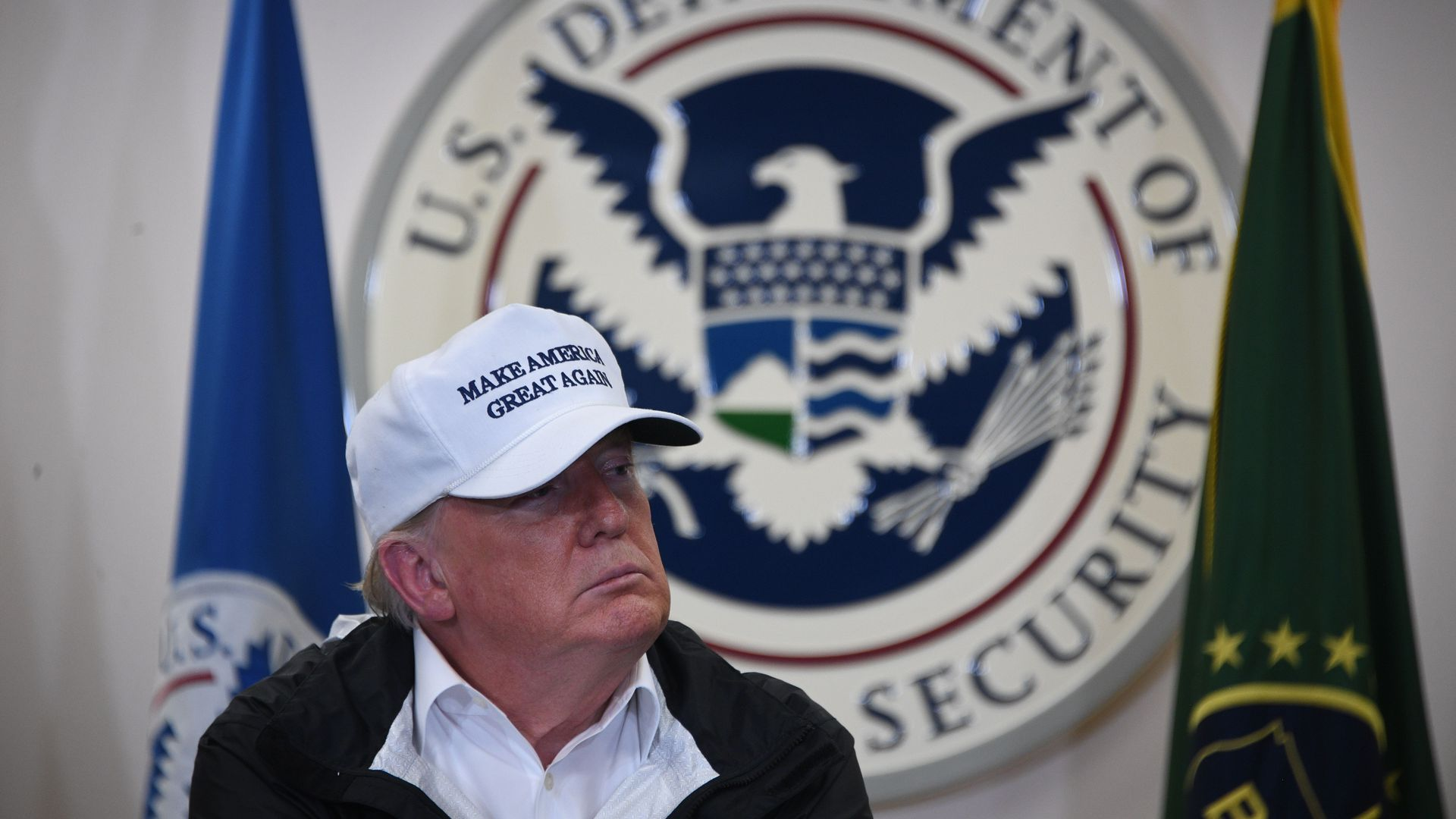 Trump sits with a white MAGA hat on in front of the logo for the US Department of Homeland Security