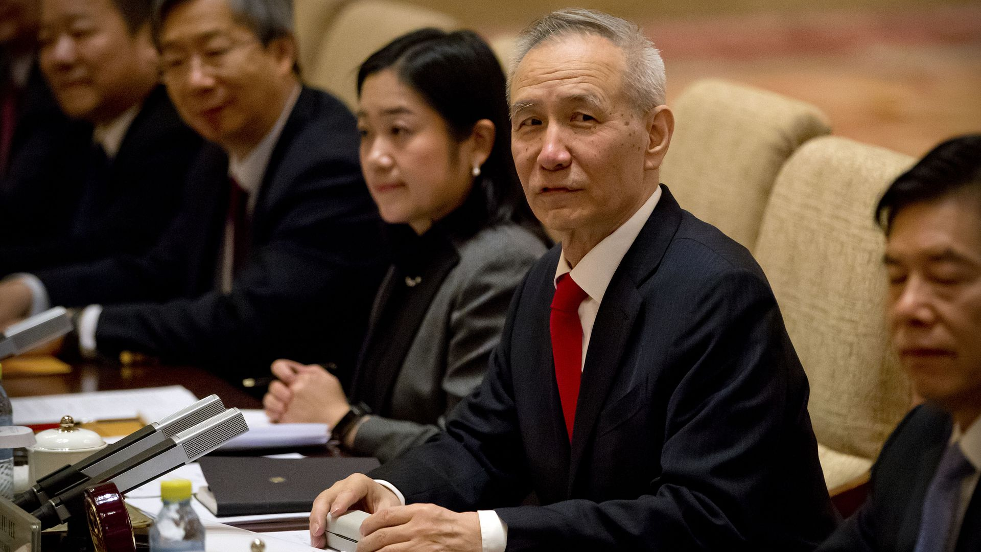 In this image, Vice Premier Liu He sits at a conference table in a beige chair next to other professionally dressed men and women.