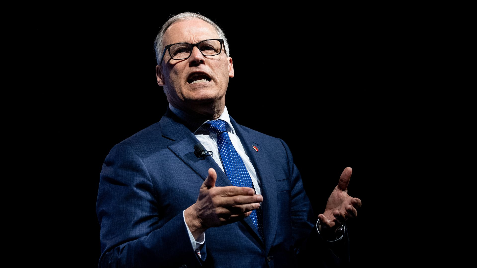 In this image, Jay Inslee speaks in a suit and tie while gesturing both hands.