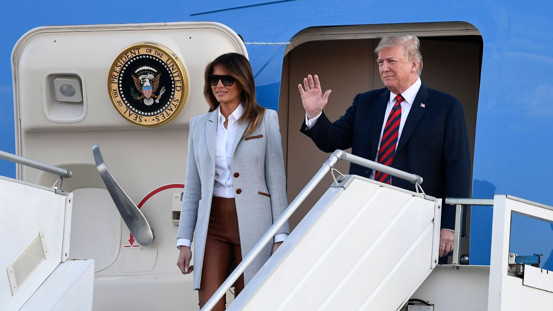 Melania and Trump on Air Force One staircase waving.