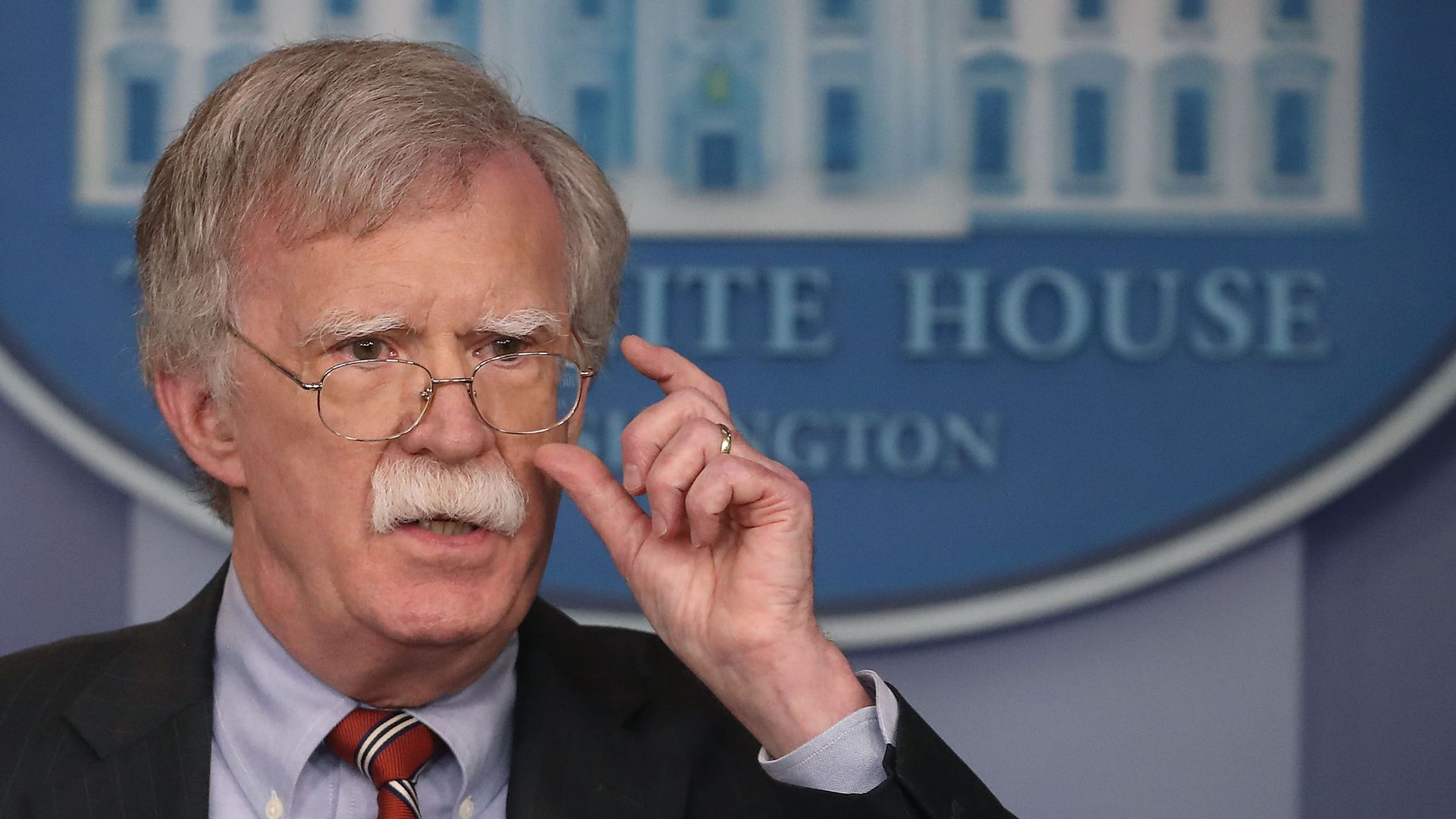 John Bolton at the White House, with his hand near his glasses
