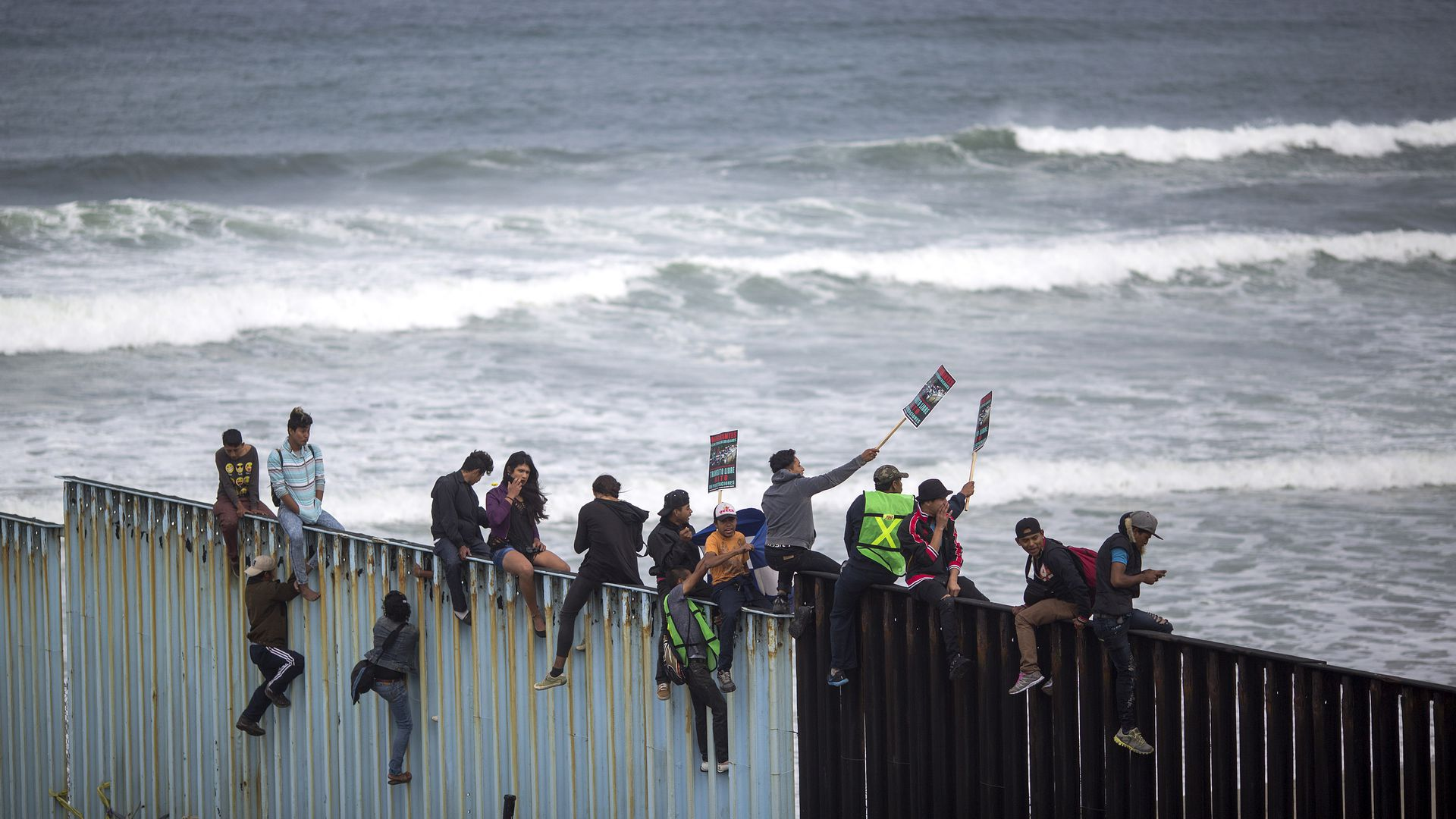 People climb a section of border fence to look toward supporters in the U.S.