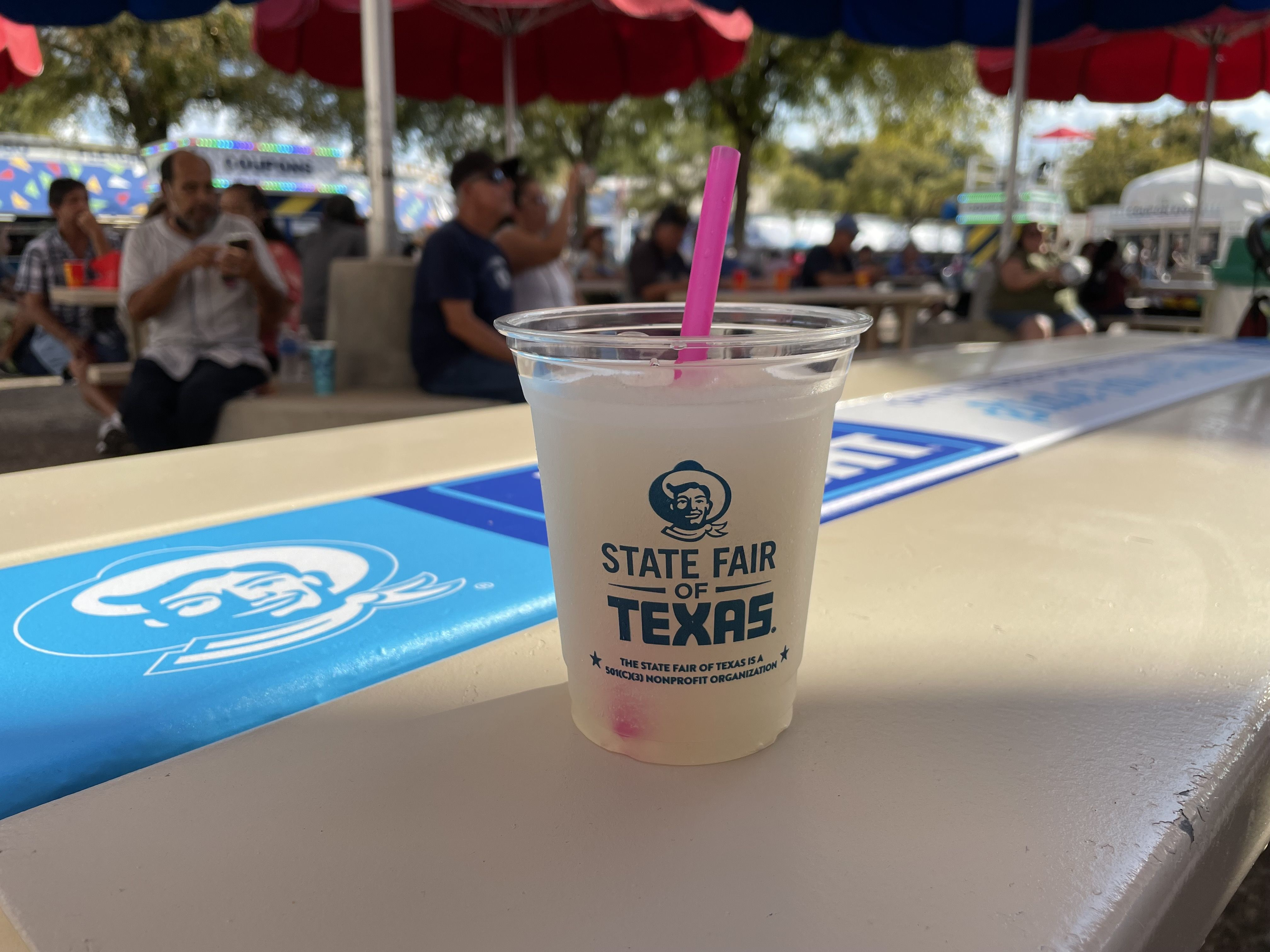 A plastic cup filled with a frozen yellow beverage and a pink straw in an outdoor setting.