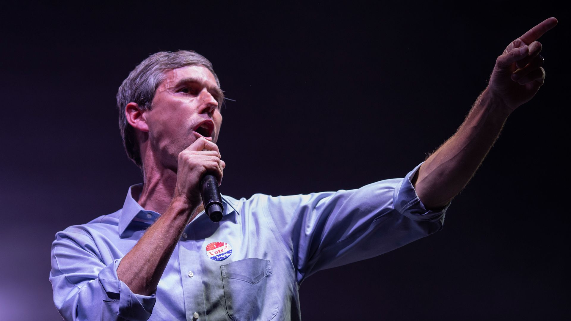 Beto O'Rourke standing on stage with a microphone in his hand