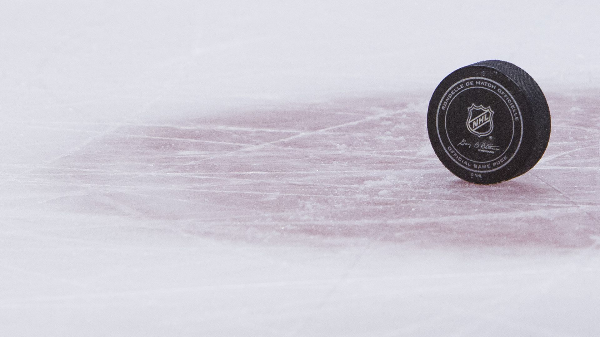 Hockey puck upright on ice