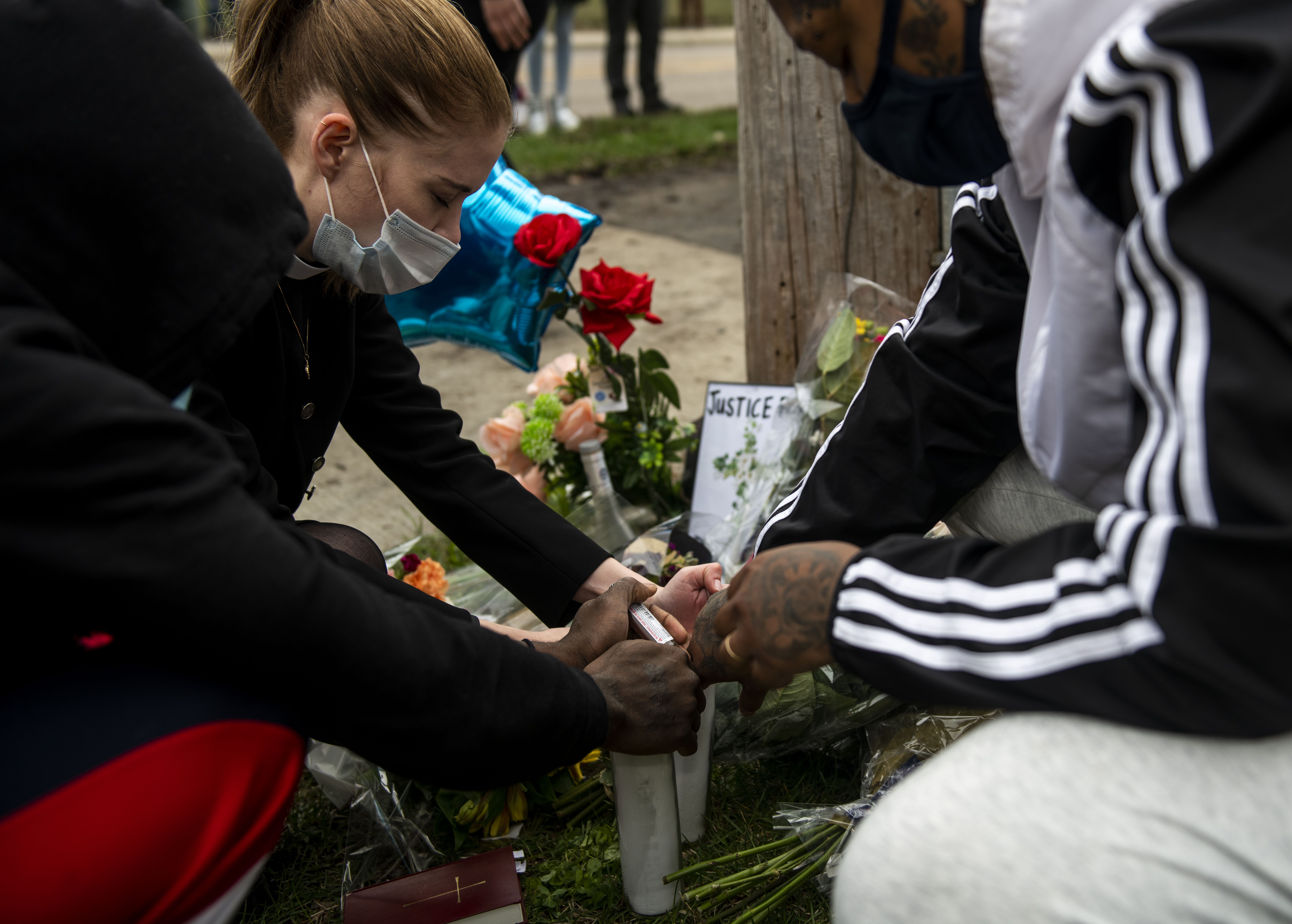 People pray over candles during a vigil for Daunte Wright on April 12, 2021 in Brooklyn Center