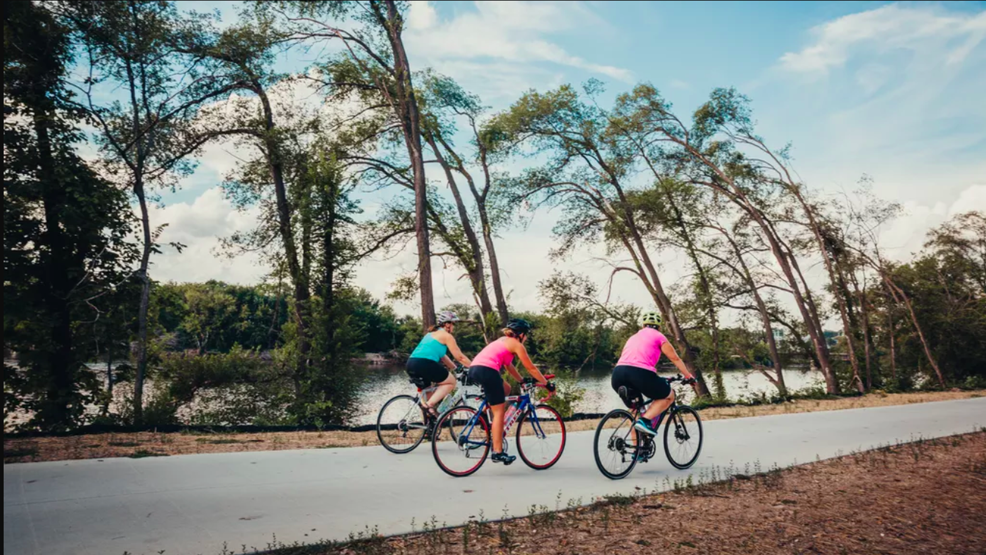 In this image, three bicyclists in brightly colored shirts and black shorts bike down a wooded street.