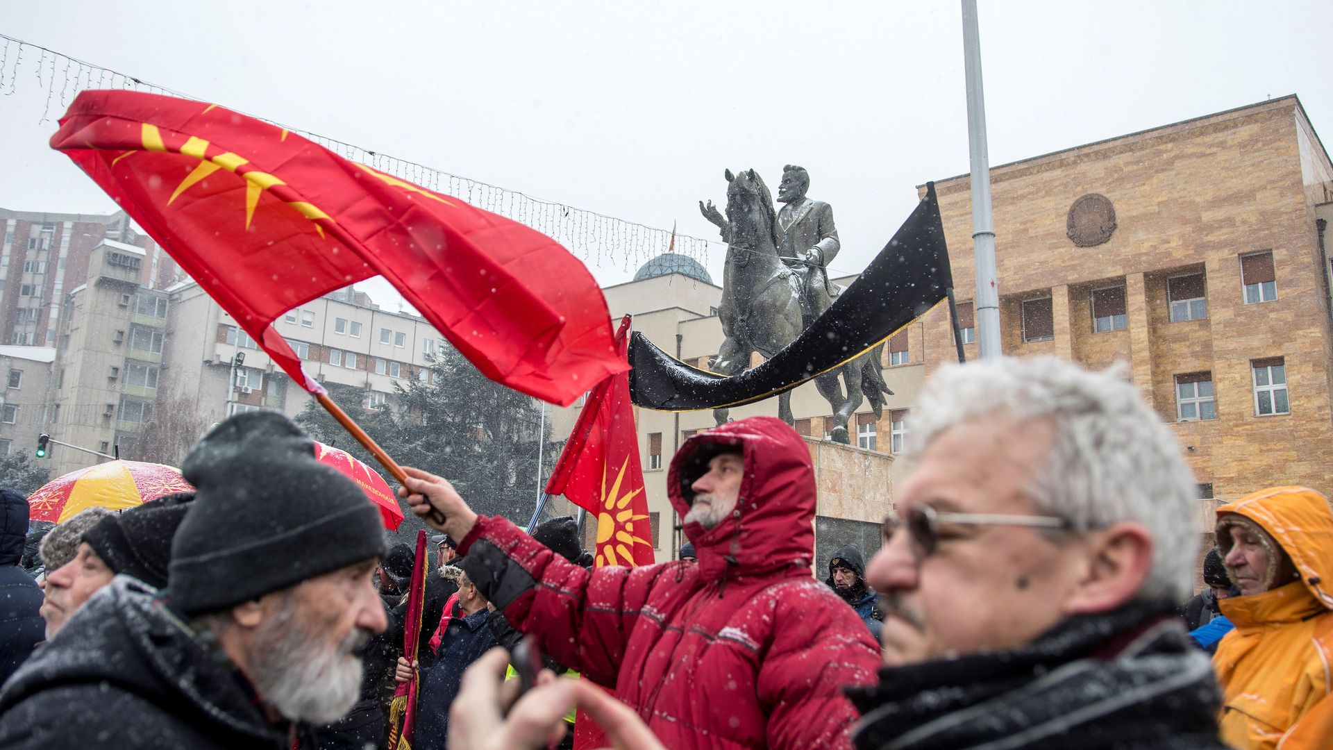 A demonstrator waves the old Macedonian flag during a protest against a process of renaming the country's name in front of the Parliament building.