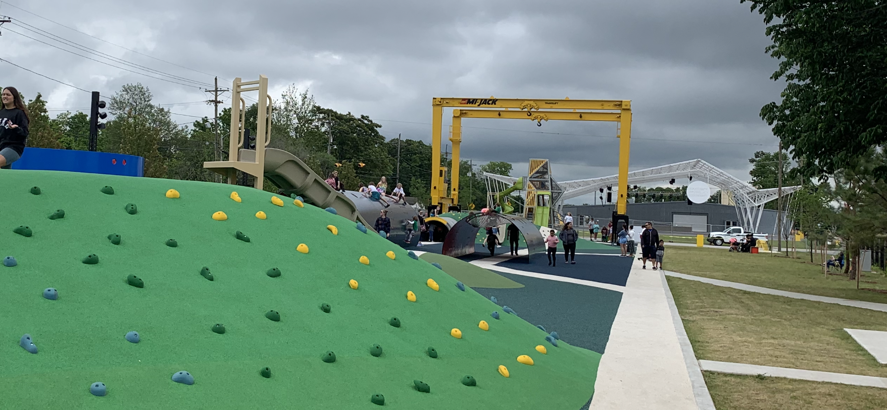 A playground area with a small rock wall and slide at Railyard Park in Rogers