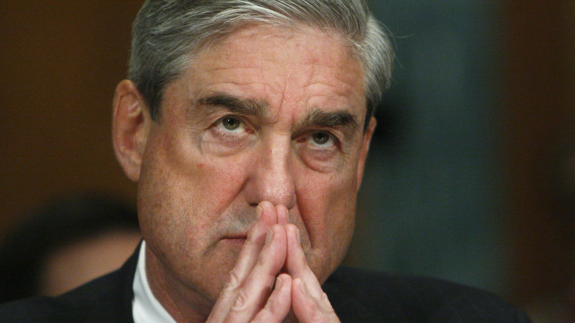 In this image, Robert Mueller listens with his fingers steepled in front of him.