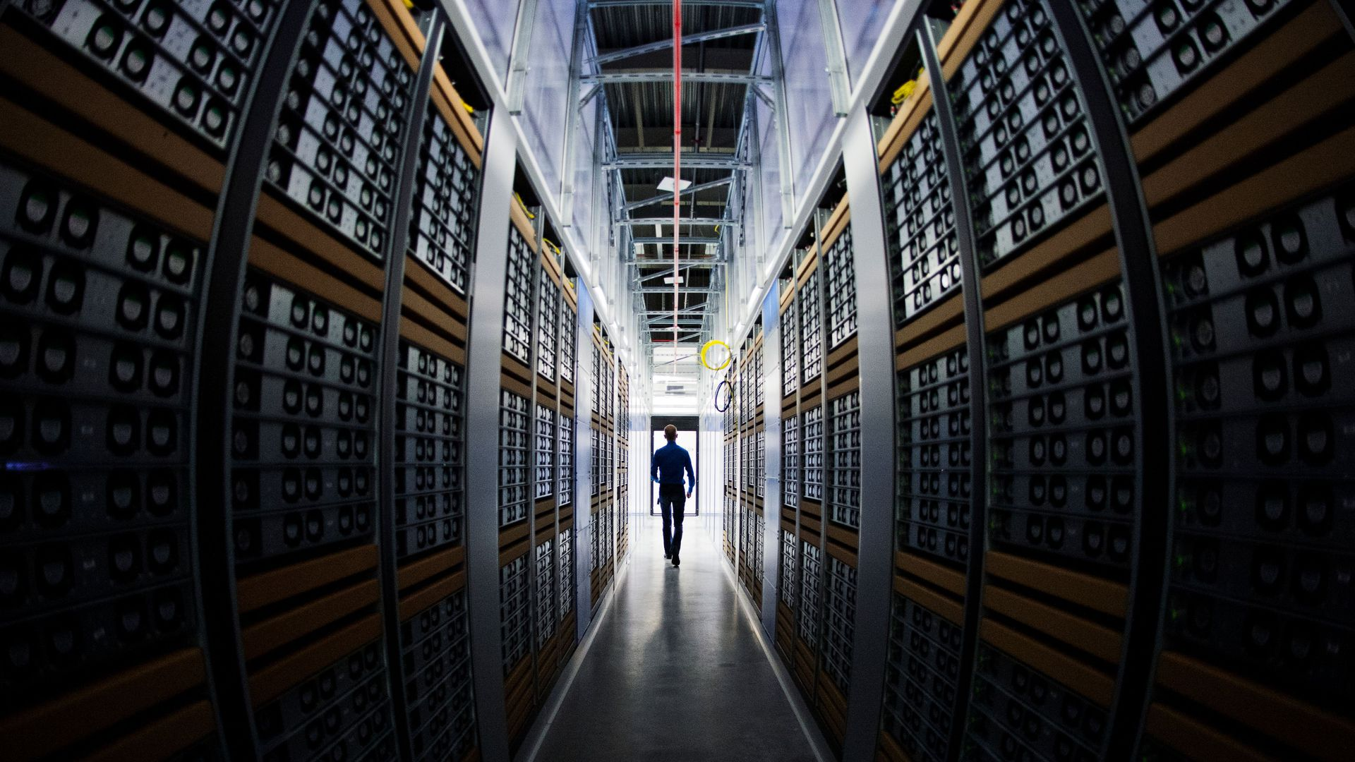 Man walking through hall of servers