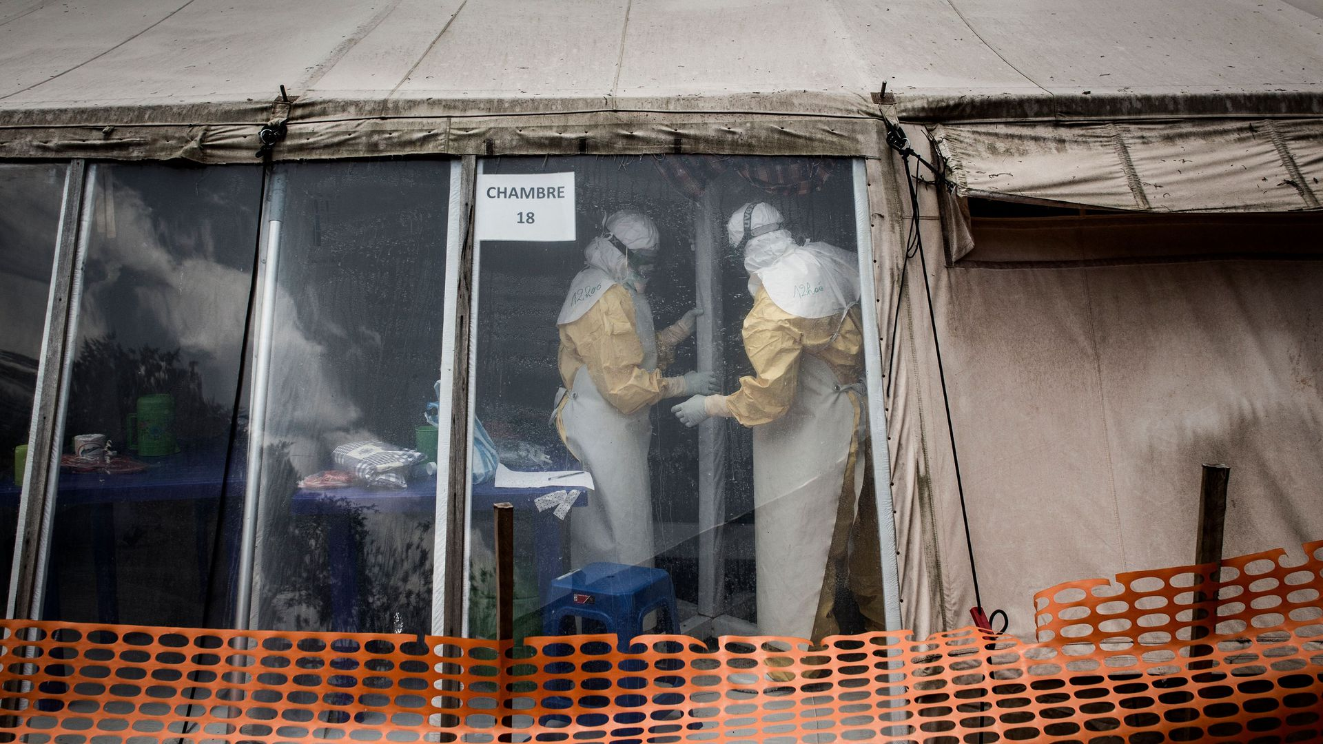 Health workers in hazmat suits are seen inside the 'red zone' of an Ebola treatment centre, behind an orange barrier.