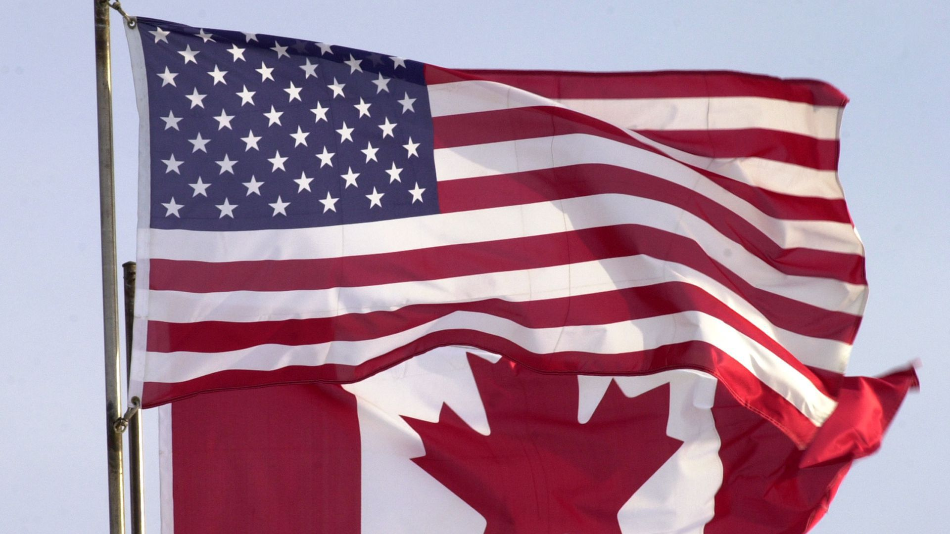 A photo of the Canadian flag flying behind the U.S. flag.