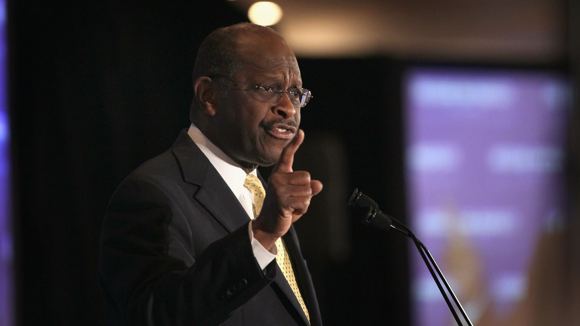 In this image, Herman Cain points a finger in the air while speaking into a microphone.