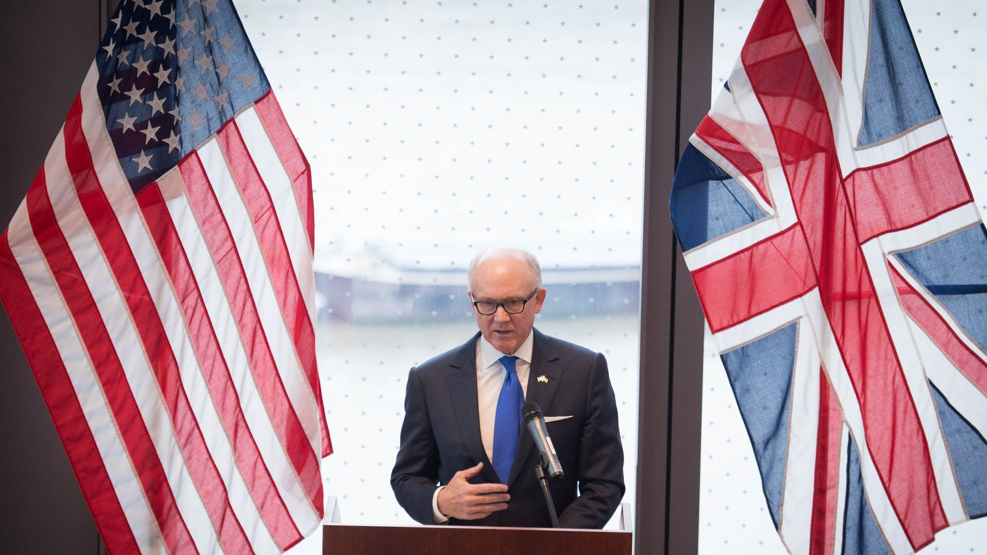 Woody Johnson in between an American and British flag