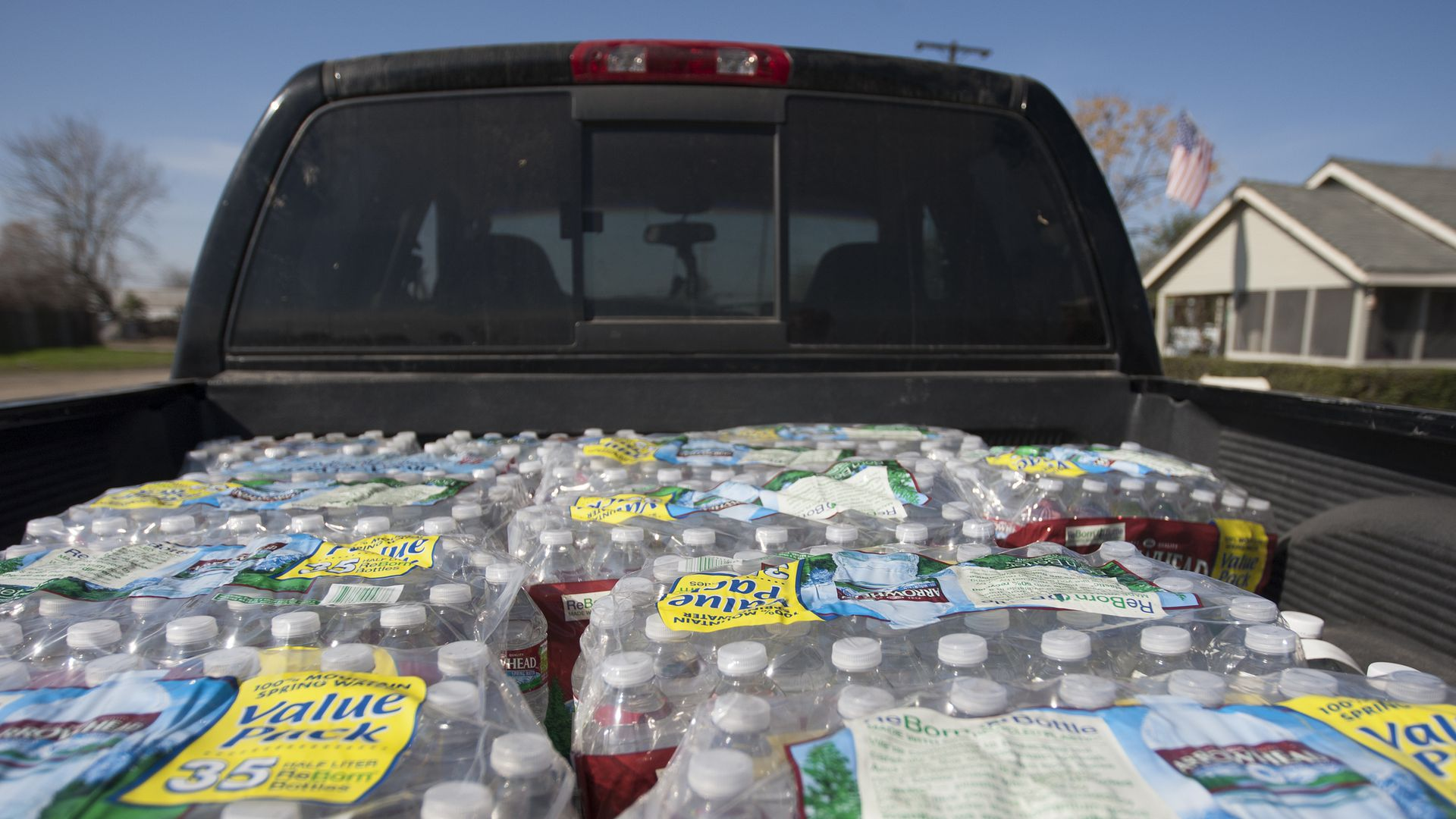 Cases of bottled water in a truck bed.