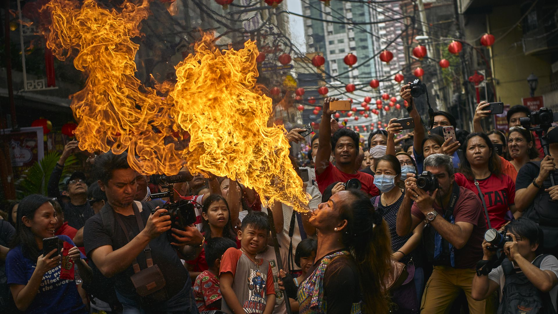 In this image, a man breathes fire as a dragon dancer celebrating the Lunar New Year