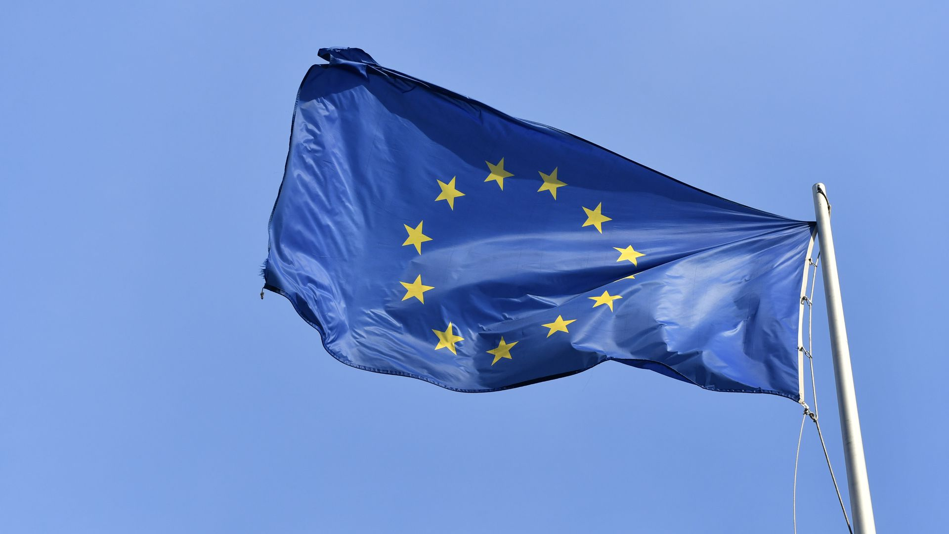 The blue and yellow flag of the European Union waves against the sky.