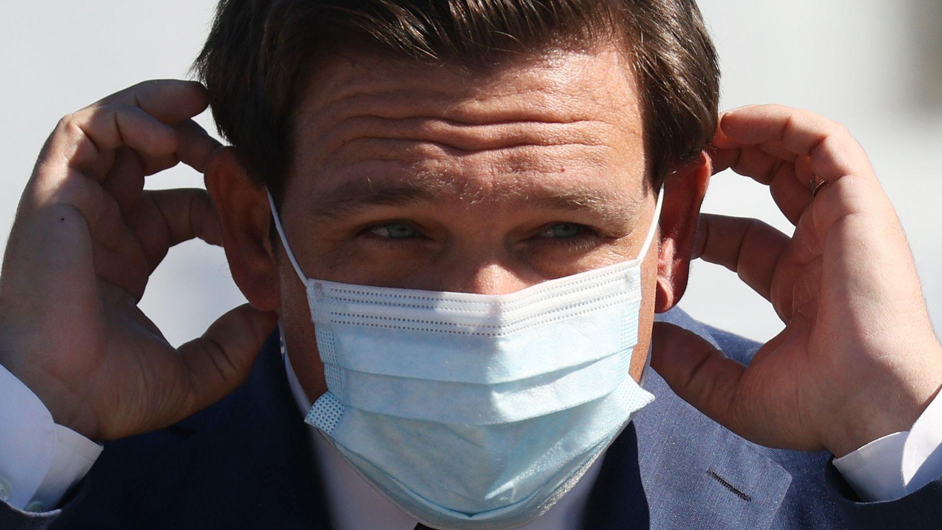 Picture of Florida Gov. Ron DeSantis putting on a mask