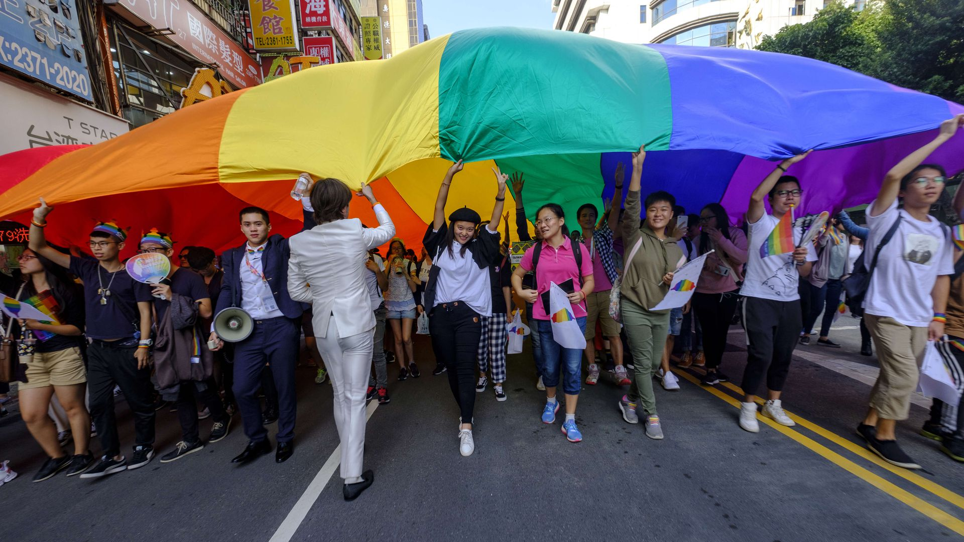 In this image, a line of demonstrators walk down the street carrying a large rainbow flag aloft.