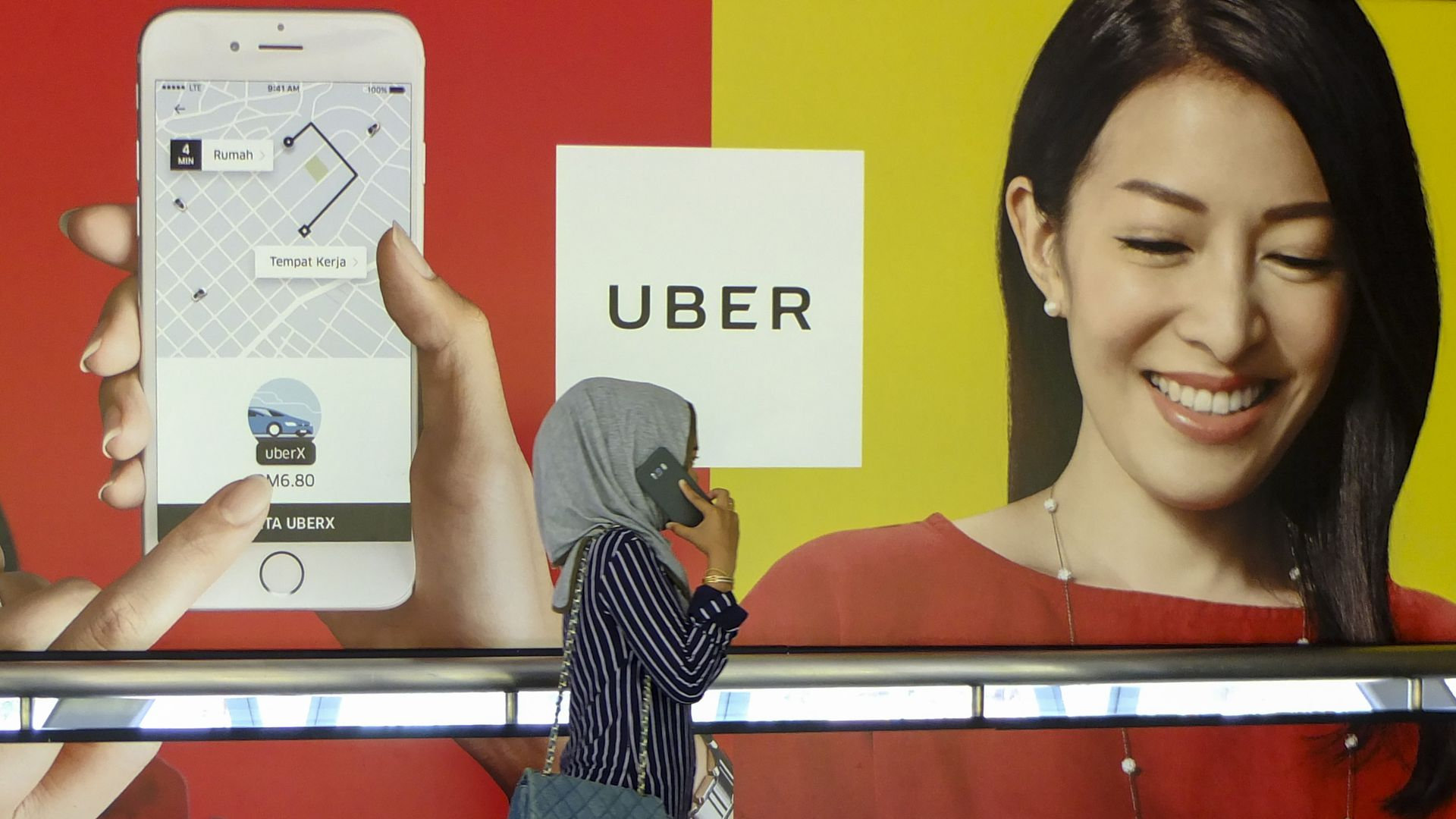 A woman on the phone walks by an Uber advertisement.