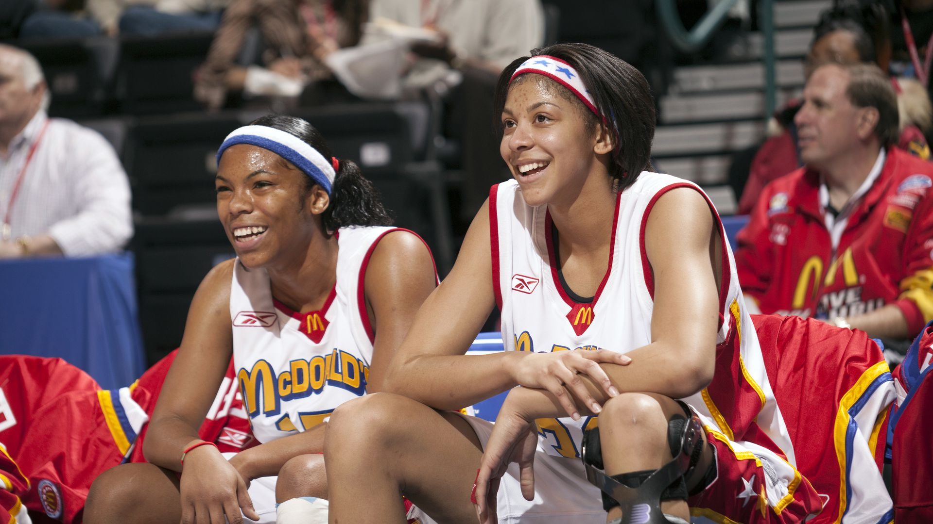 Candace Parker sits on a chair at a basketball game.