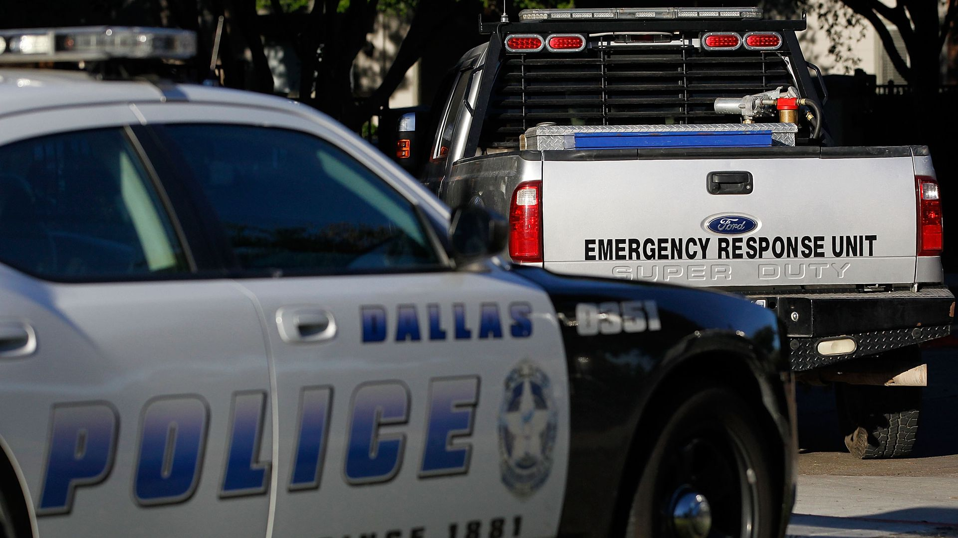 A truck with the words EMERGENCY RESPONSE UNIT is parked in front of a Dallas Police squad car.