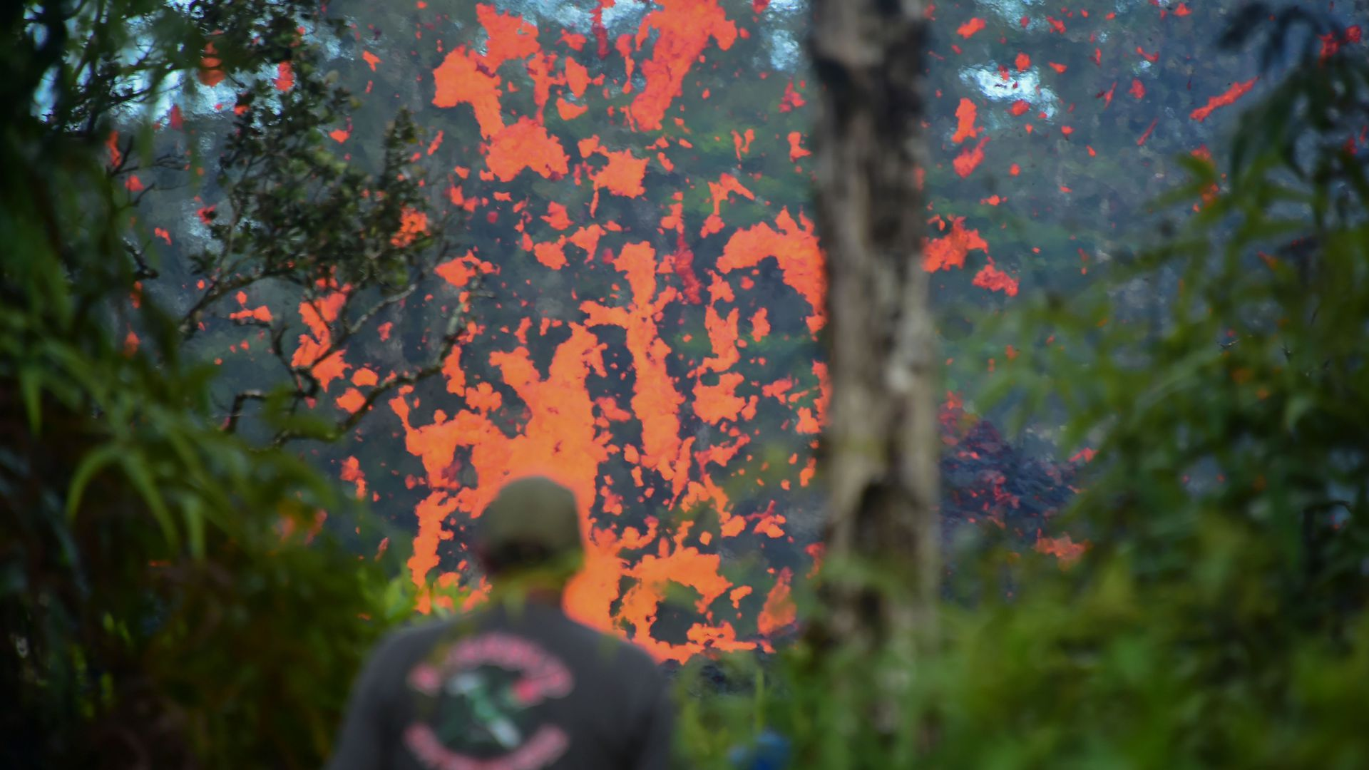A man watches as lava is seen coming from a fissure