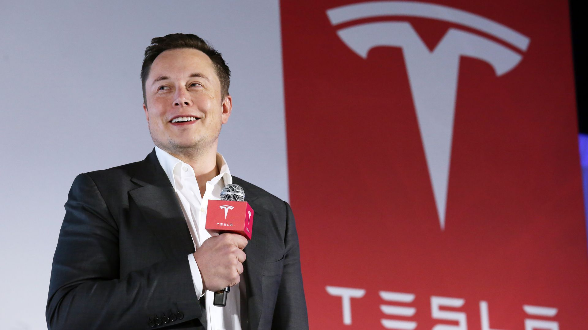 In this image, Elon Musk stands in a suit with a microphone in front of a red sign depicting the Tesla logo.