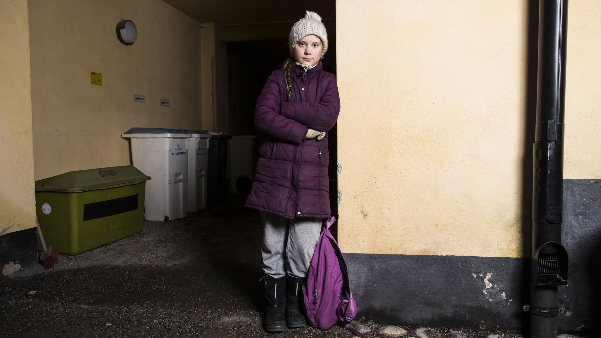 In this image, Greta stands in a puffy winter coat and hat while leaning against a wall, with a bookbag near her.
