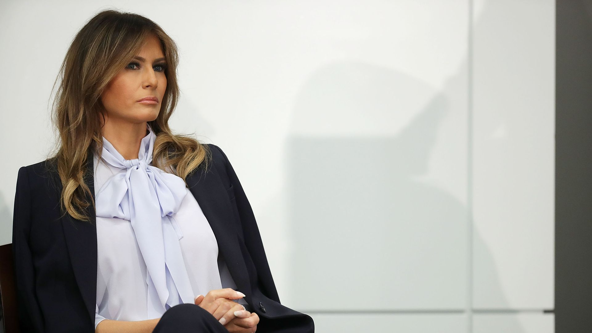 Melania Trump sitting in a chair on stage with a serious expression