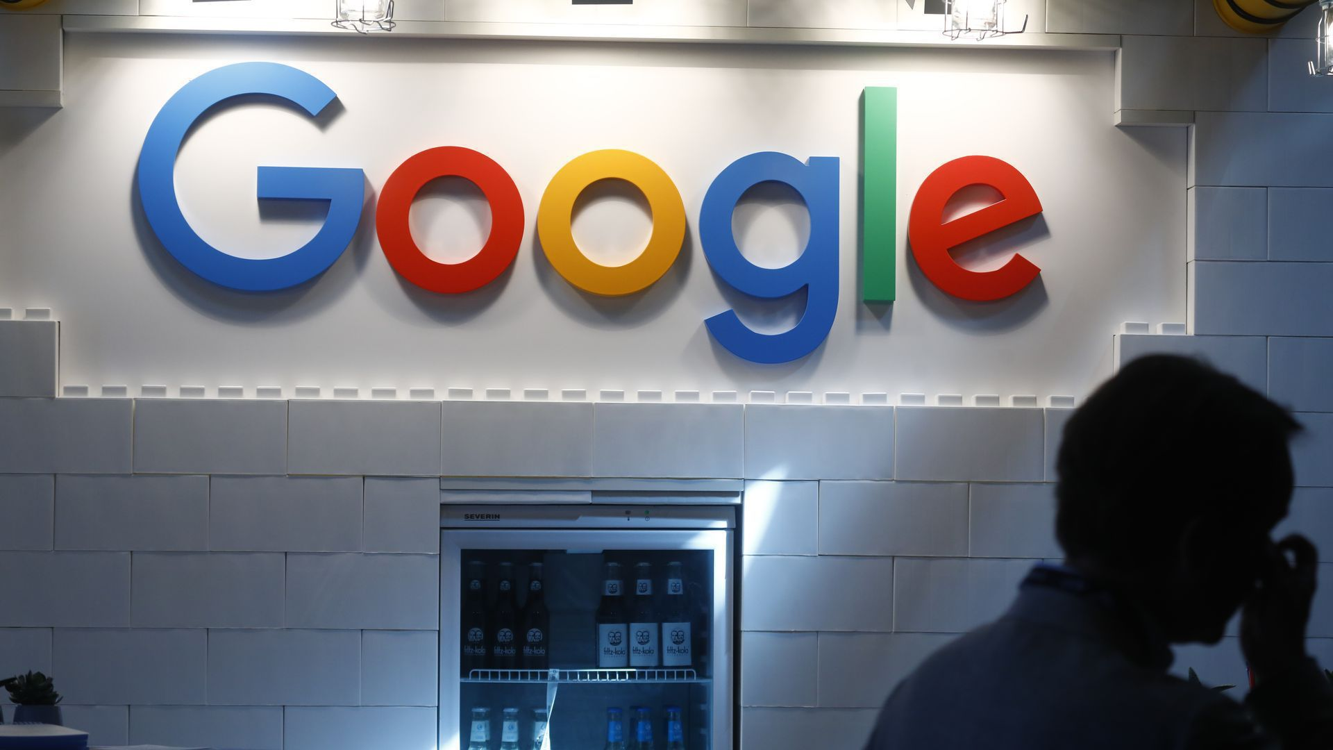 Google logo on wall over a soft-drink fridge