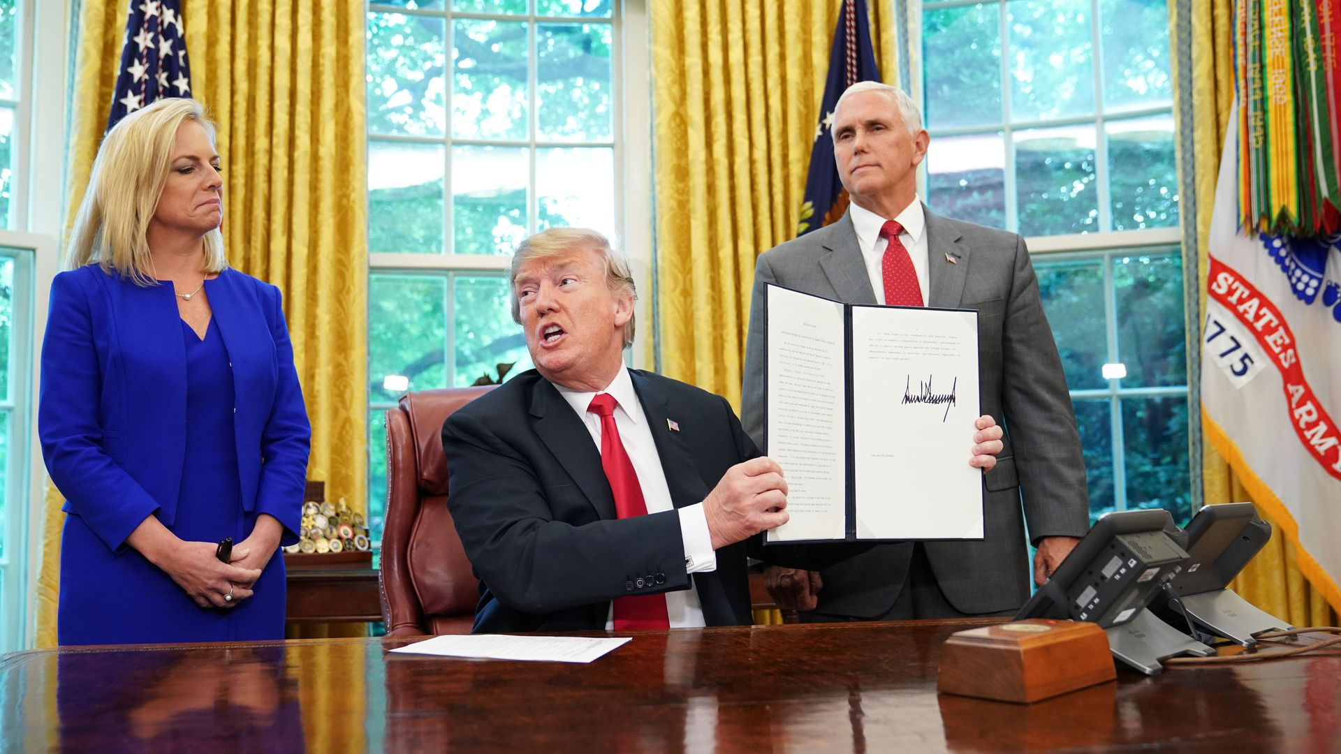 President Trump holding up a signed executive order on immigration