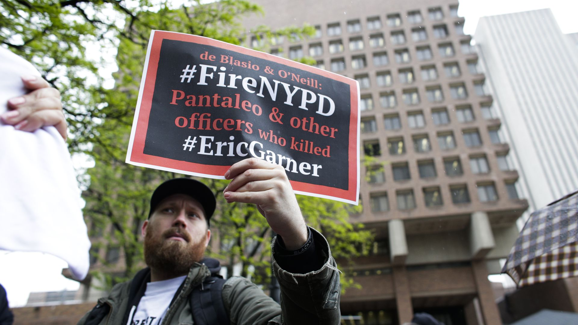Protestor holding a sign saying officers involved in Eric Garner's death should be fired