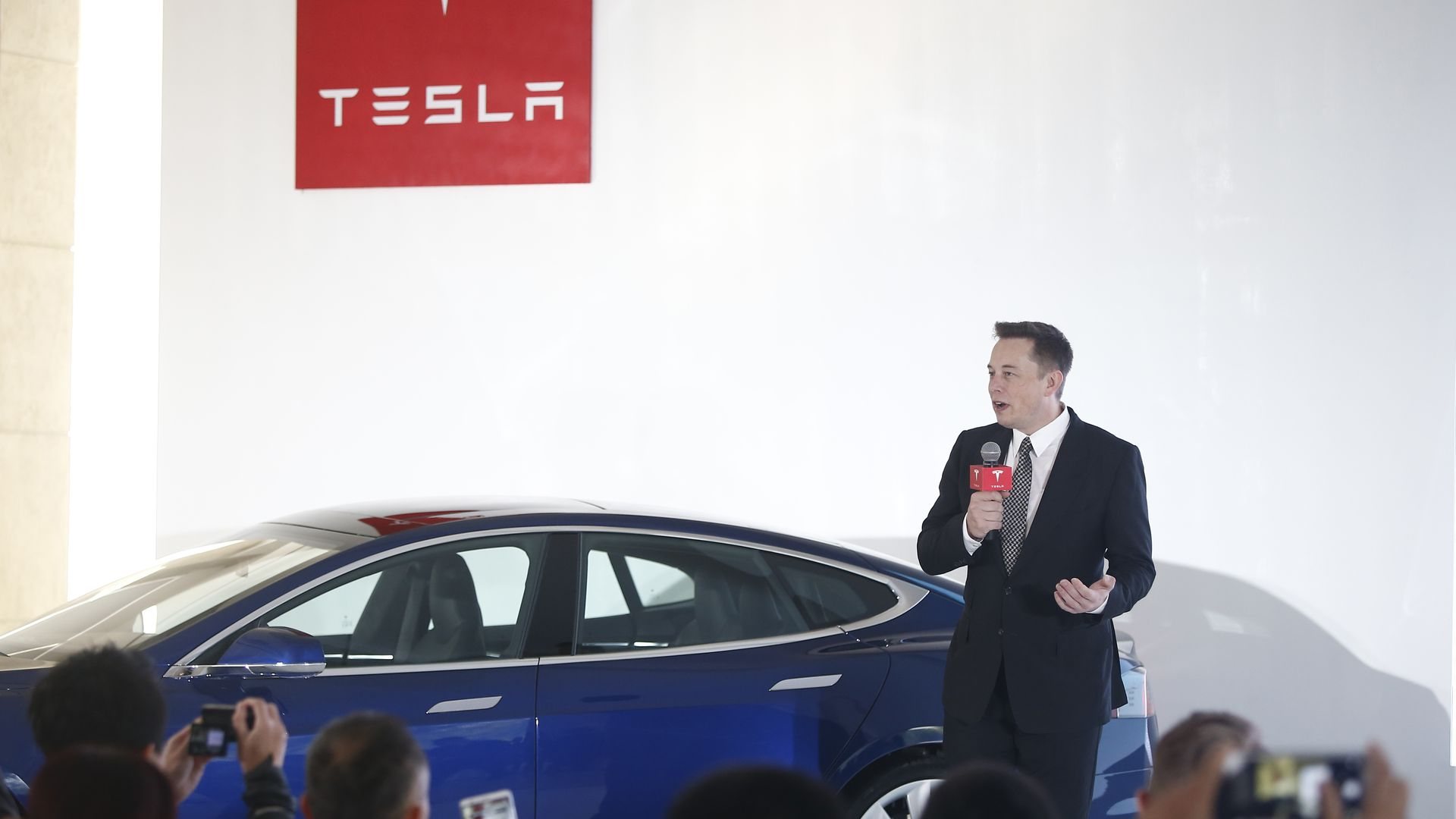 Tesla CEO Elon Musk speaking to a crowd in front of a Tesla car.