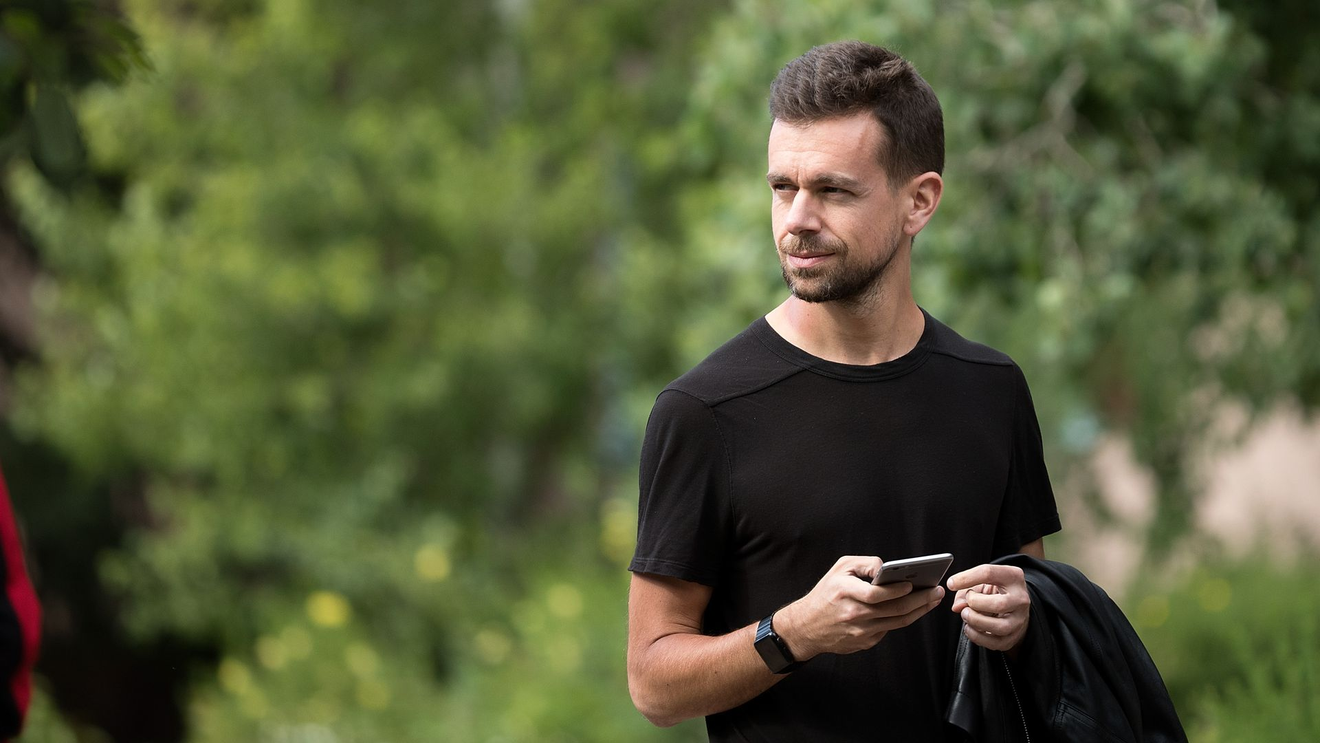 Twitter CEO Jack Dorsey wears a black t-shirt and stands outside