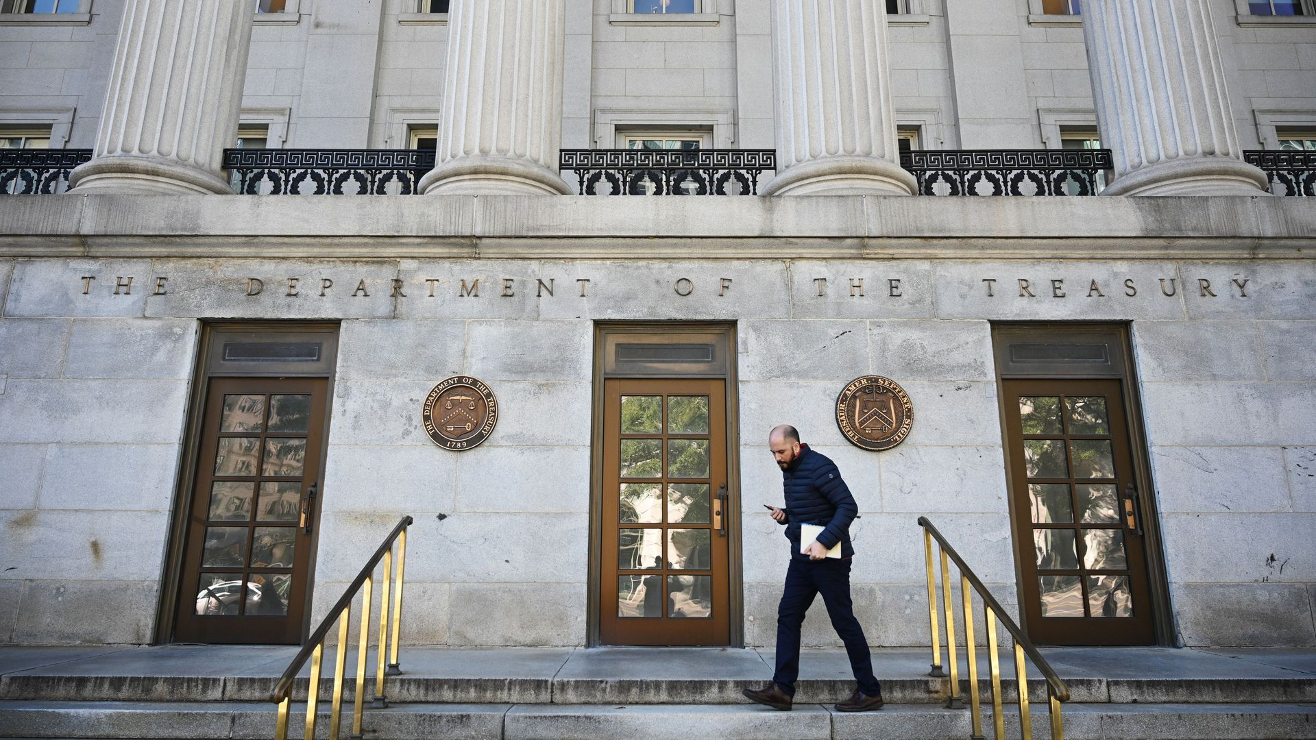 In this image, a man carrying a file walks down the front steps of the Department of Treasury building.