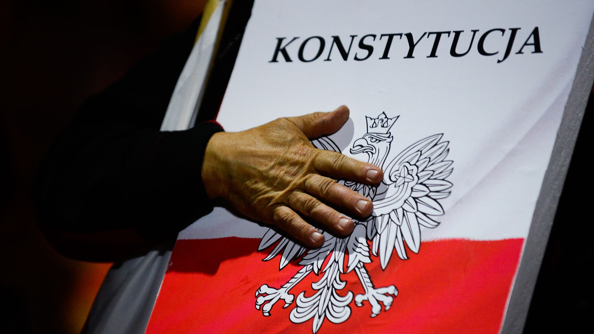 Protester with hand on Poland constitution