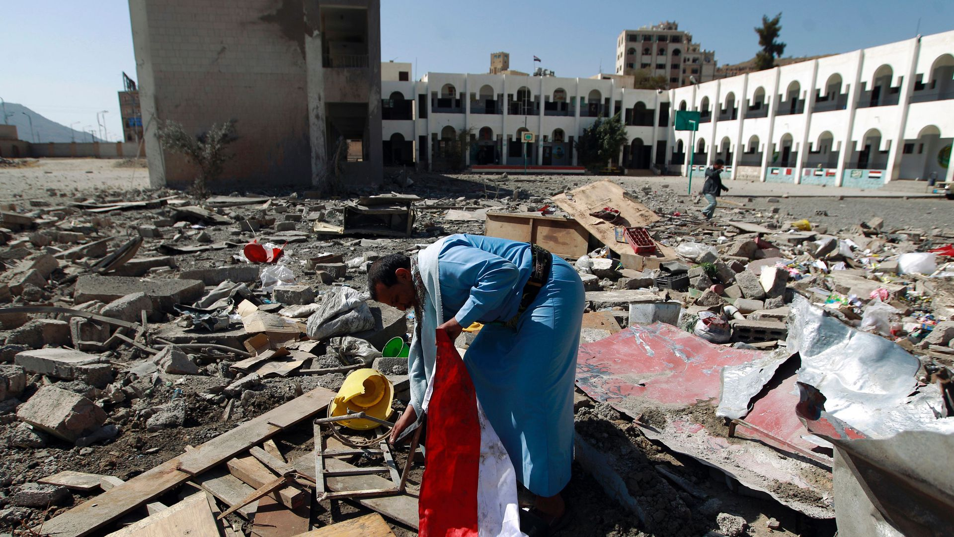 In this image, a man in Yemen holds a flag while searching through rubble.