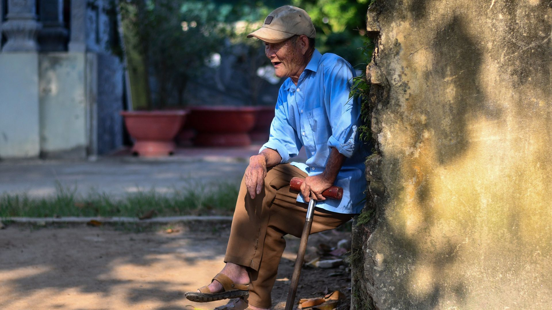 In this image, an elderly man sits outside with a stick in Vietnam