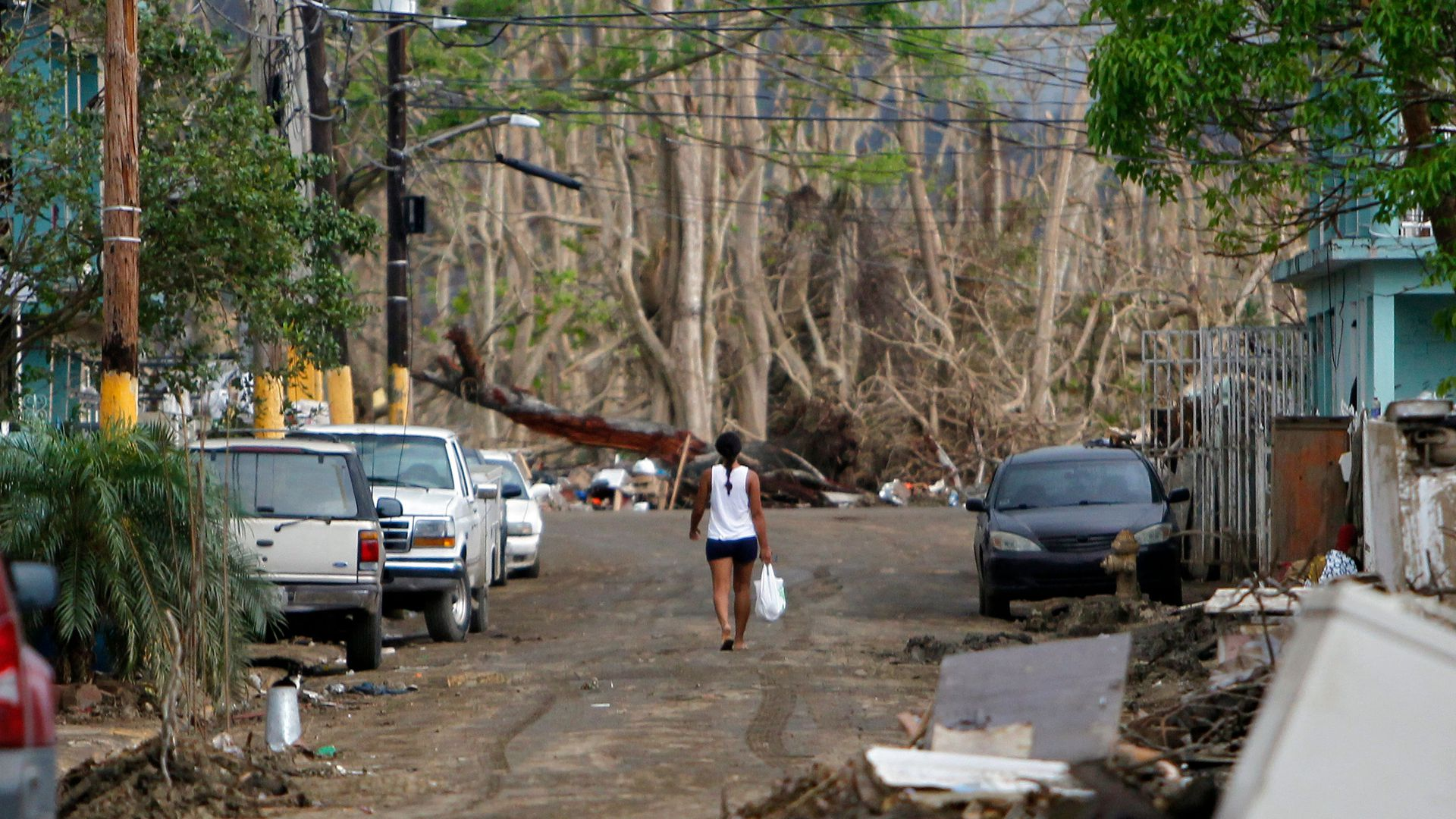 A woman in a white tank top walks down the middle of a dirt road with cars on either side.
