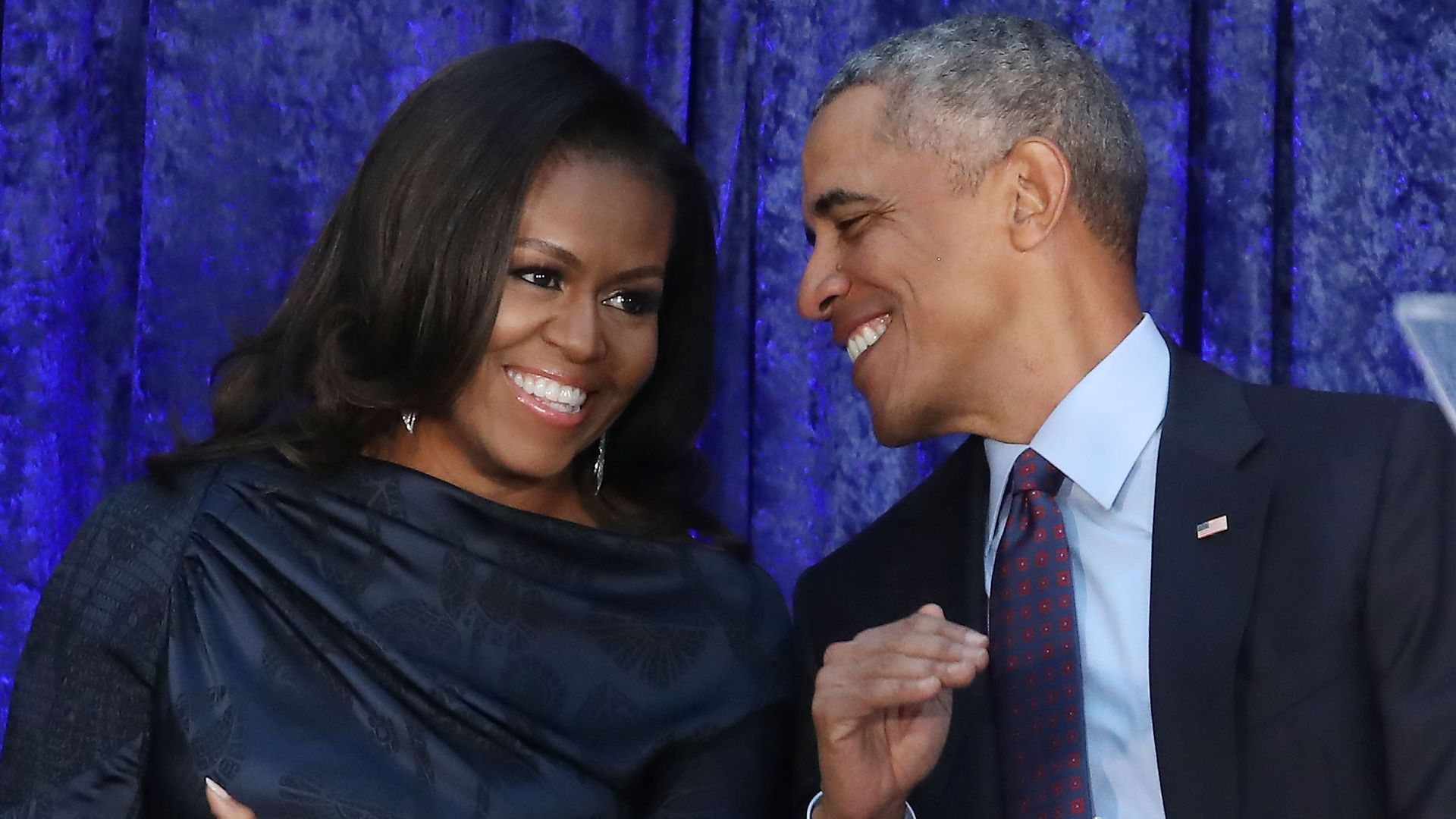 Barack and Michelle Obama sitting down next to each other and leaning toward each other laughing.