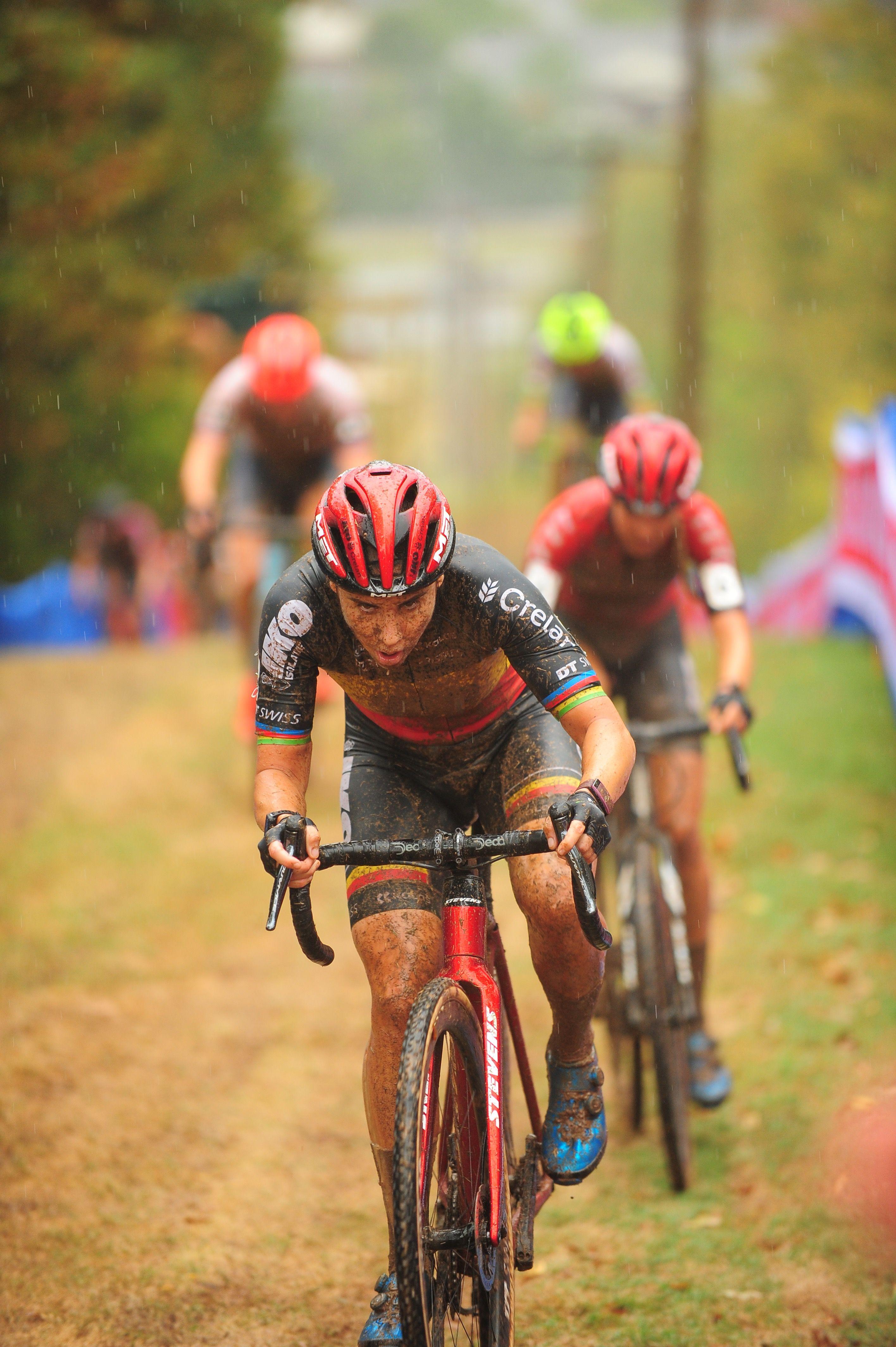 Photo of a muddy woman climbing a hill on a bike.