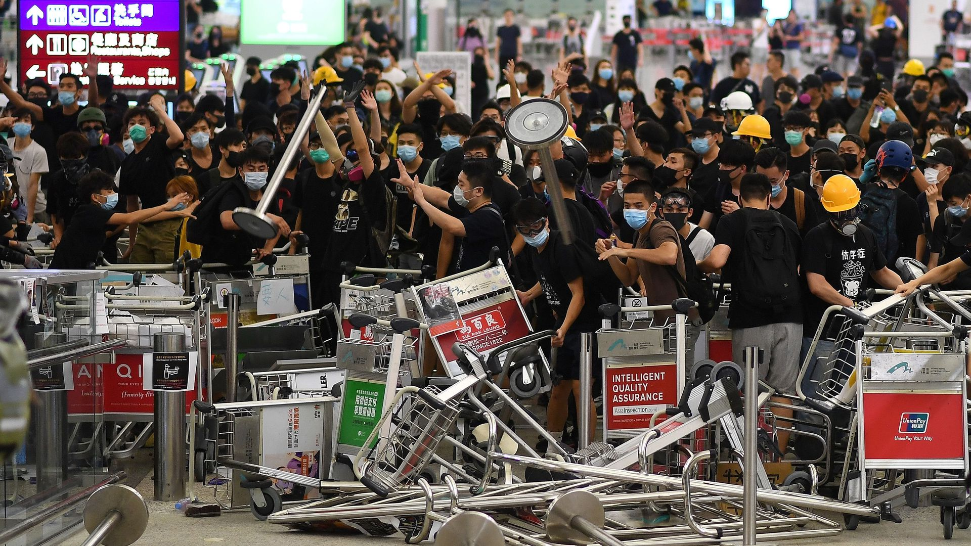 protestors create a barricade of luggage carts at the airport
