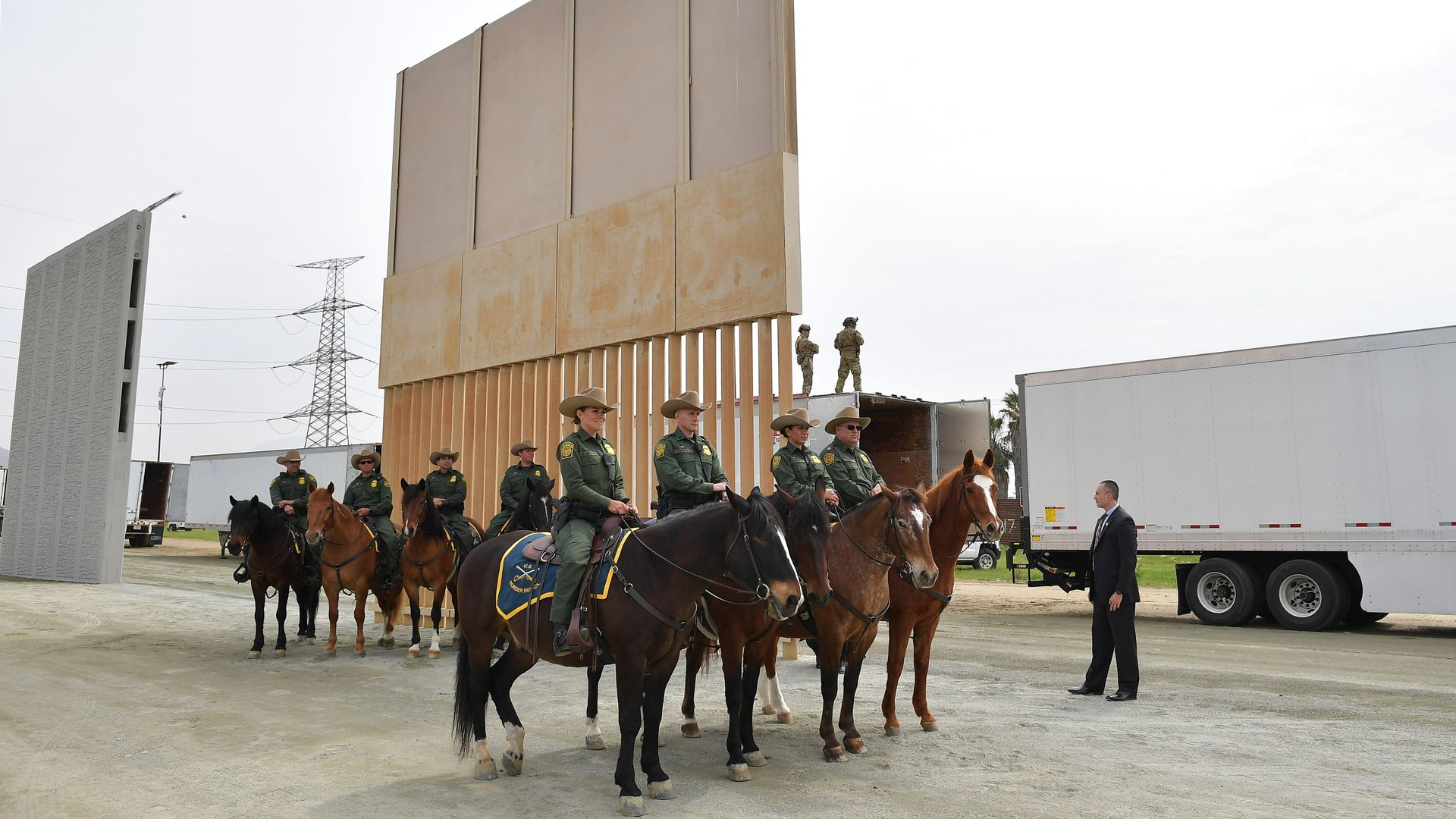 Mounted Border Patrol agents on horseback in front of a prototype of Trump's border wall