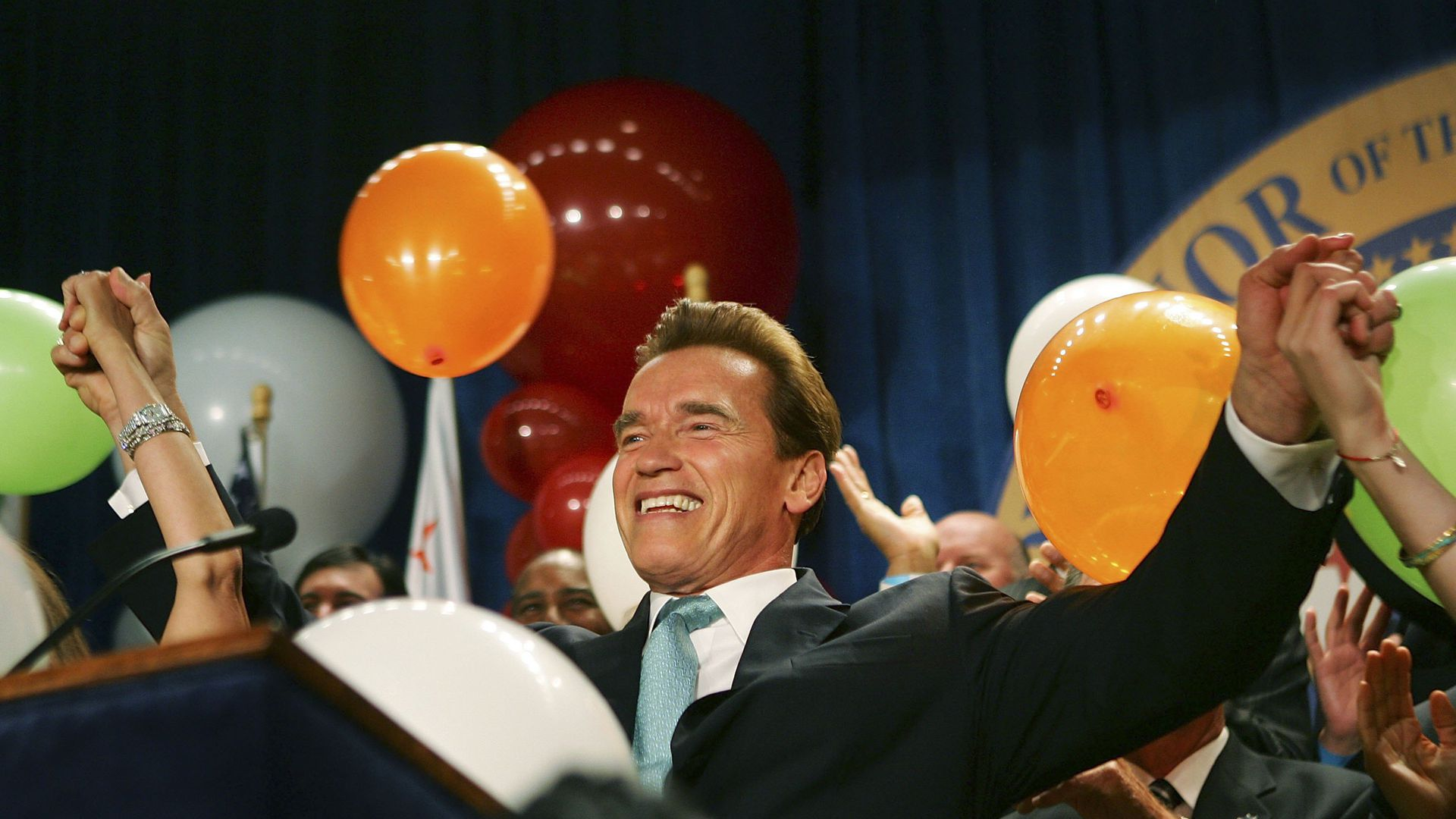 Schwarzenegger throws his hands in the air at a victory party
