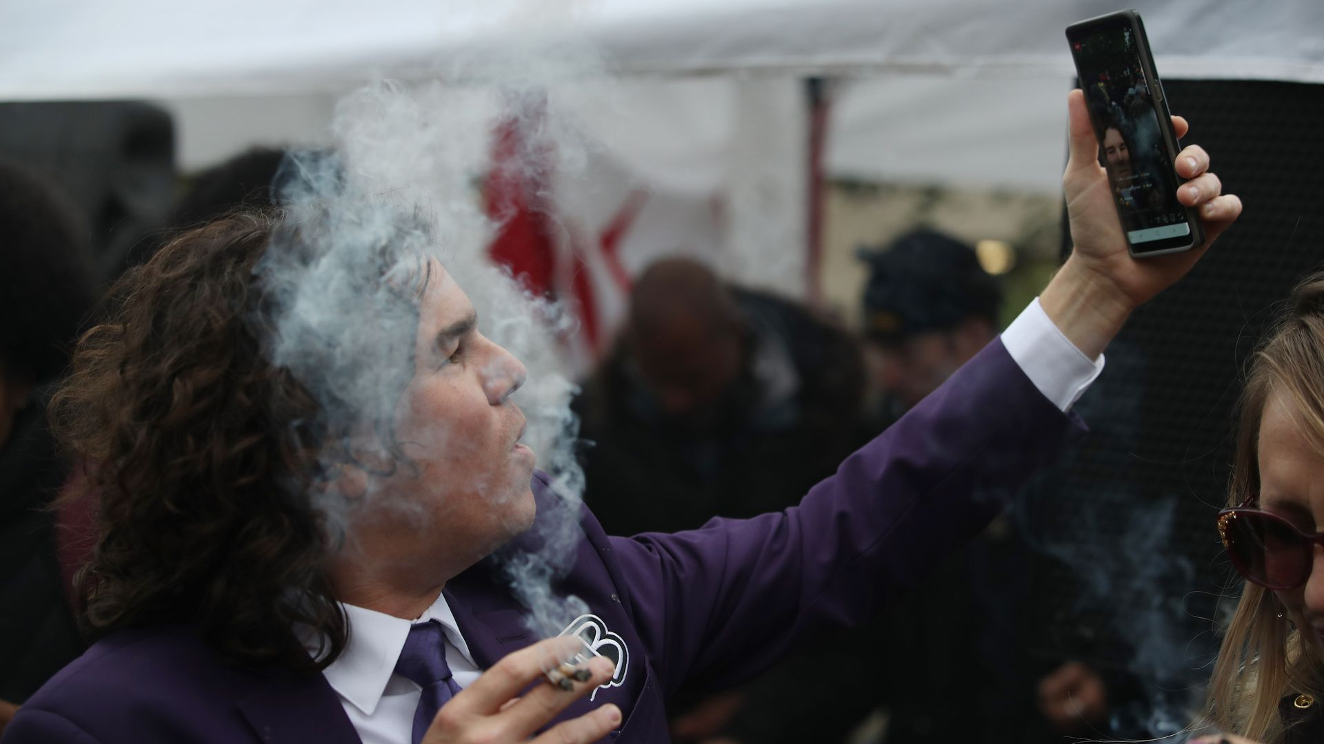 In this image, a man in a suit takes a selfie while smoking.