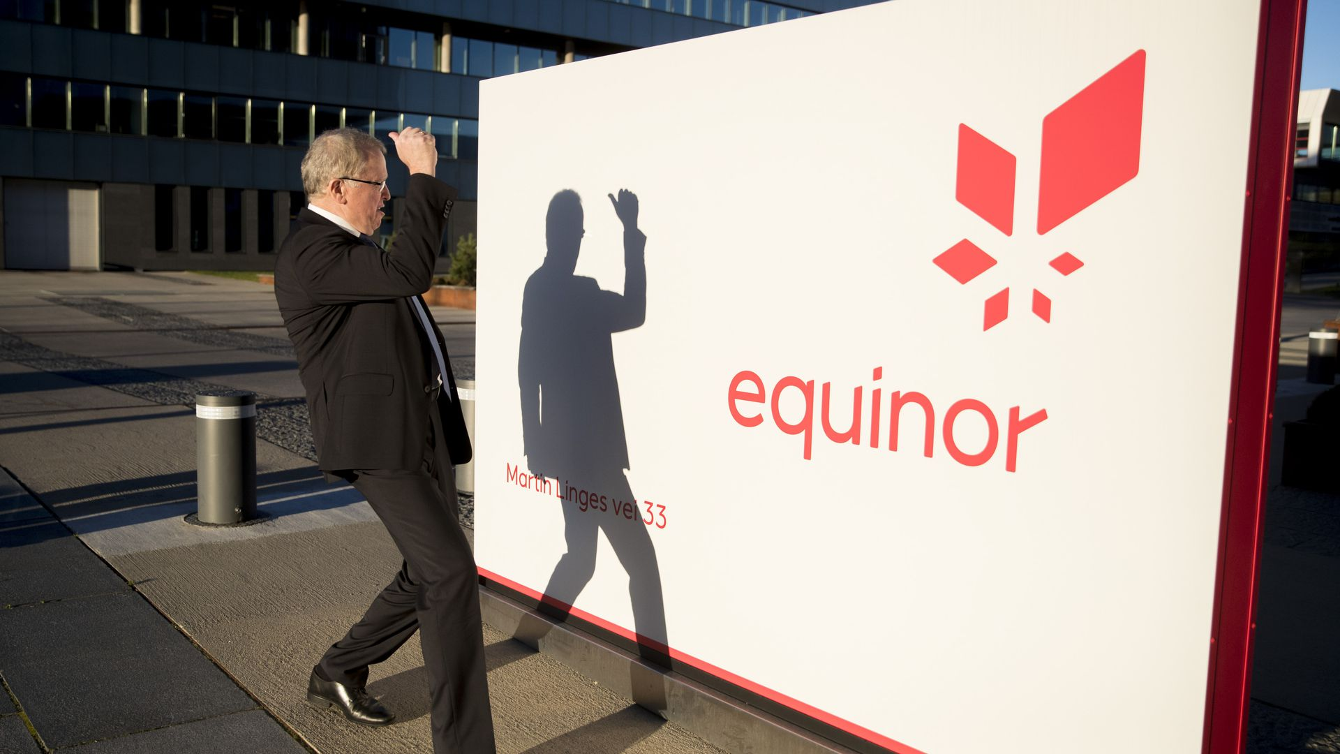 Equinor CEO looking at his shadow on an Equinor sign.