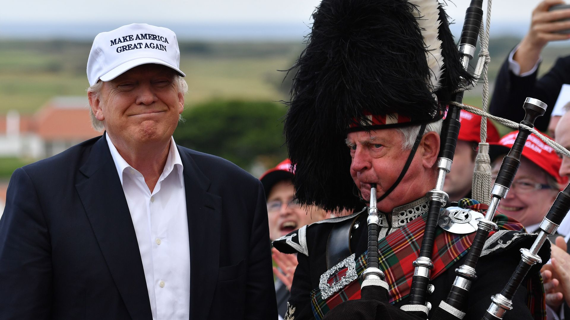 A bagpipe player next to Donald Trump as he arrives to his Trump Turnberry Resort.