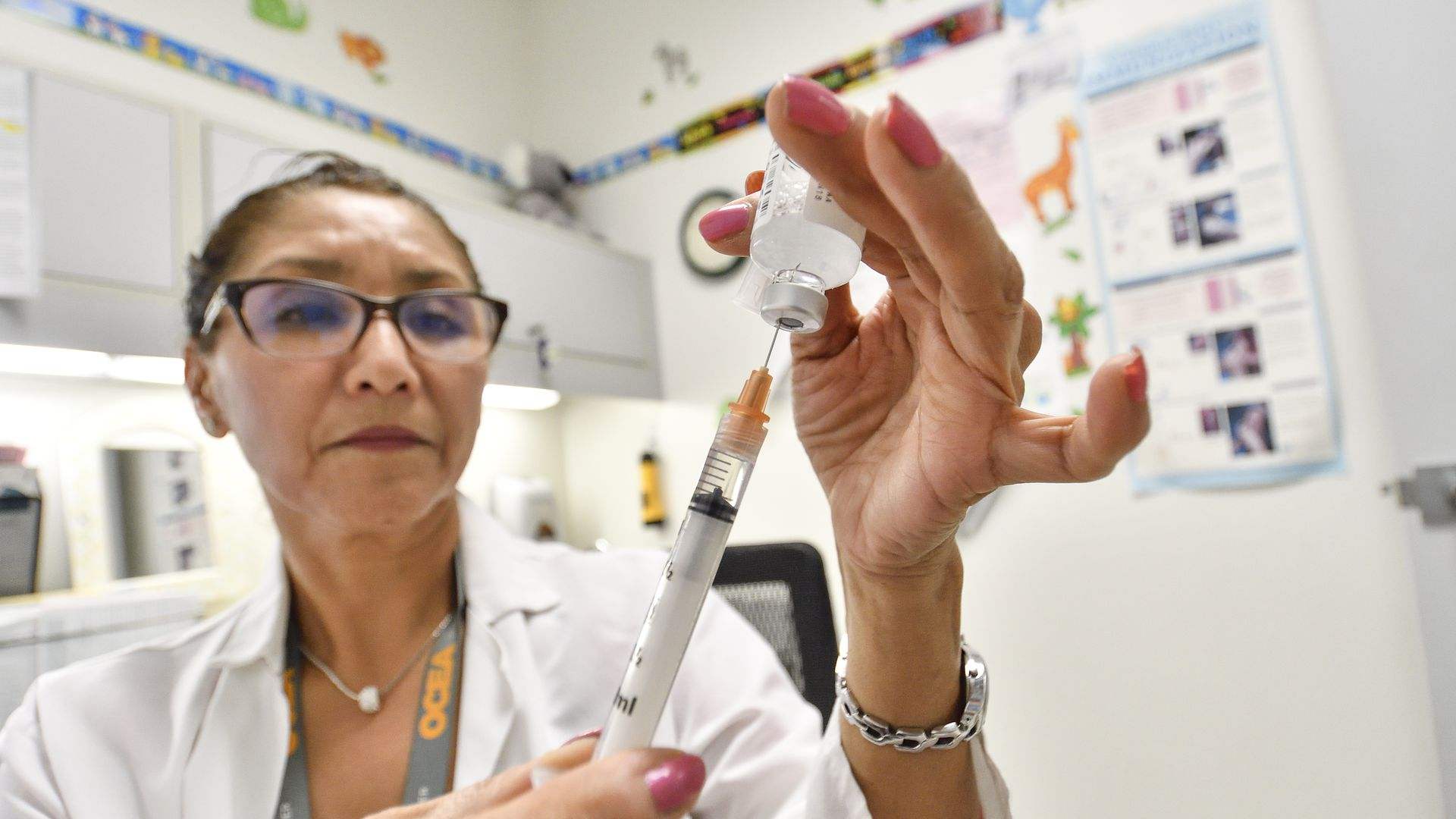 A nurse fills a syringe with the flu vaccine.